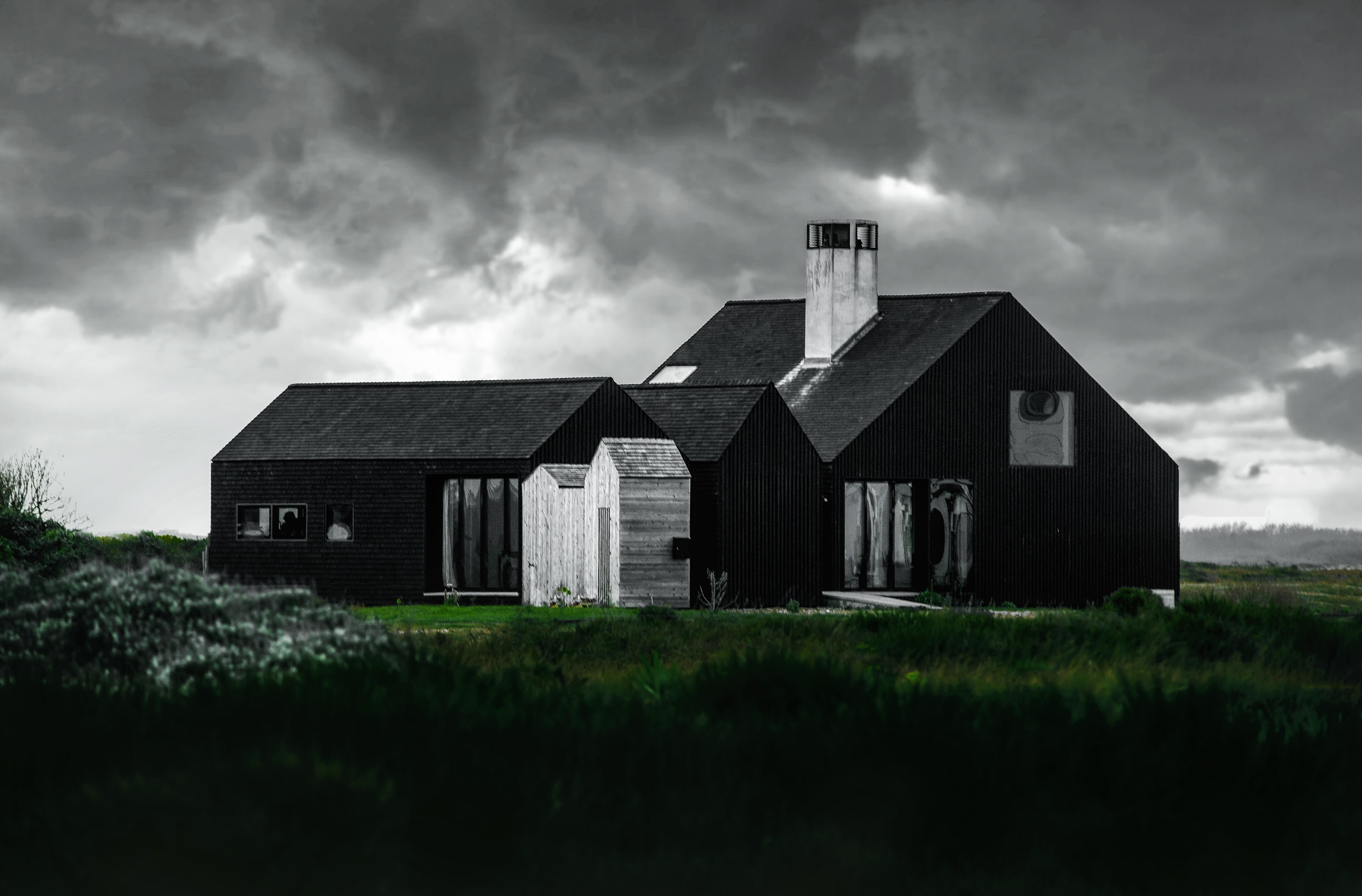 Large cabin-like wooden house with white sheds and chimneys on a grassy hill