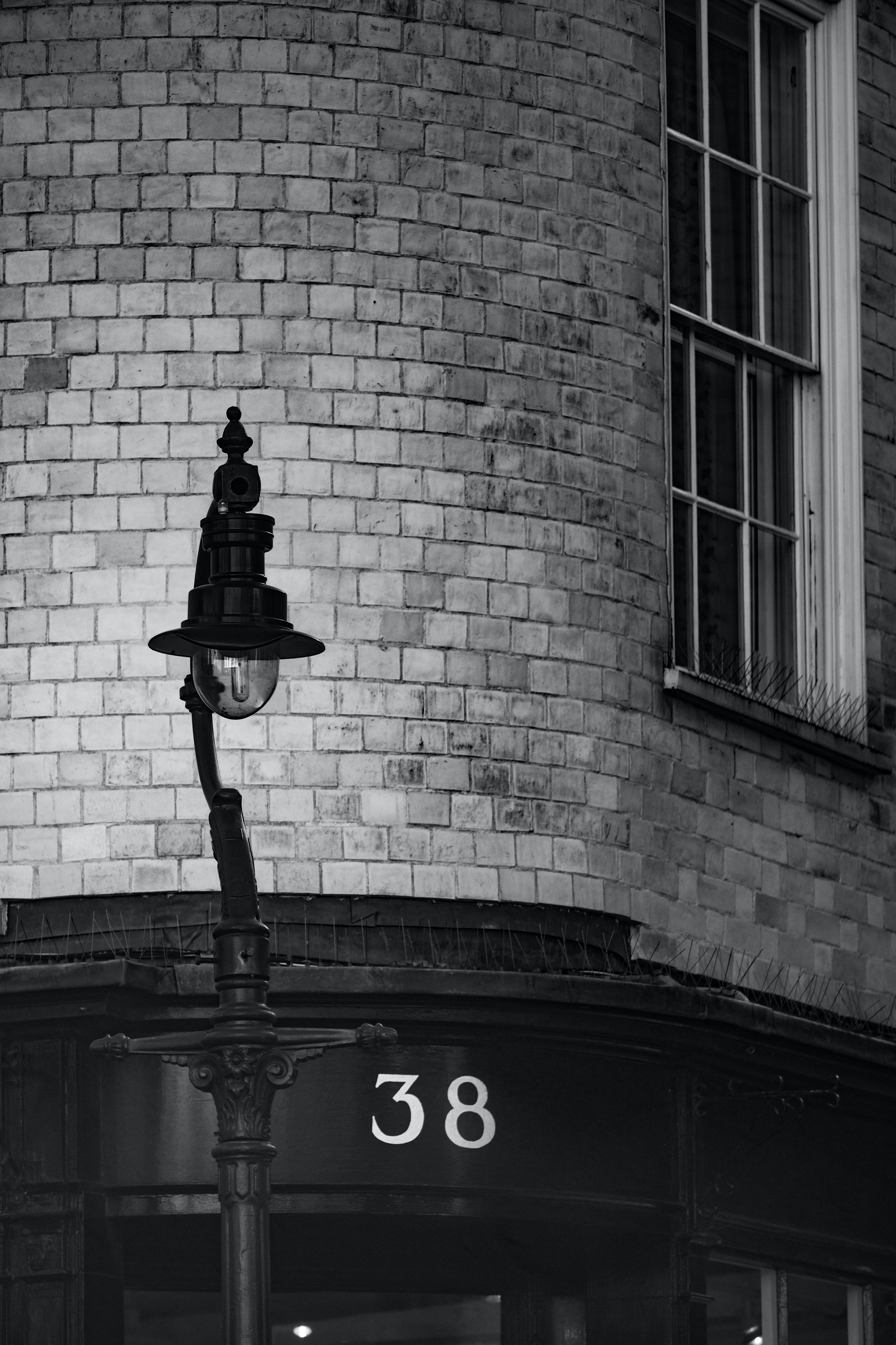 Black and white shot of traditional street light near brick building with number 38 sign
