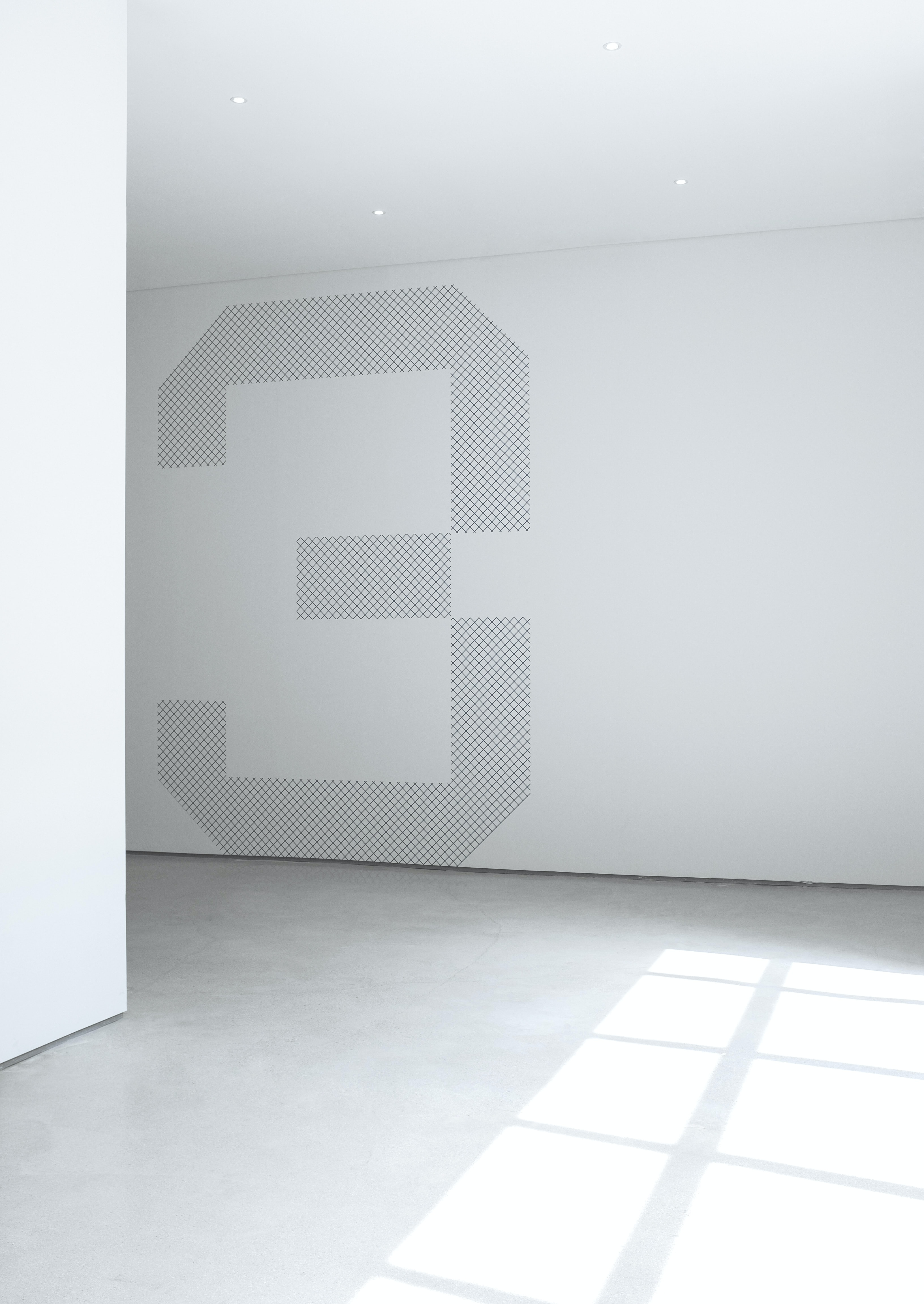 A large number three painted on a white wall in an empty room