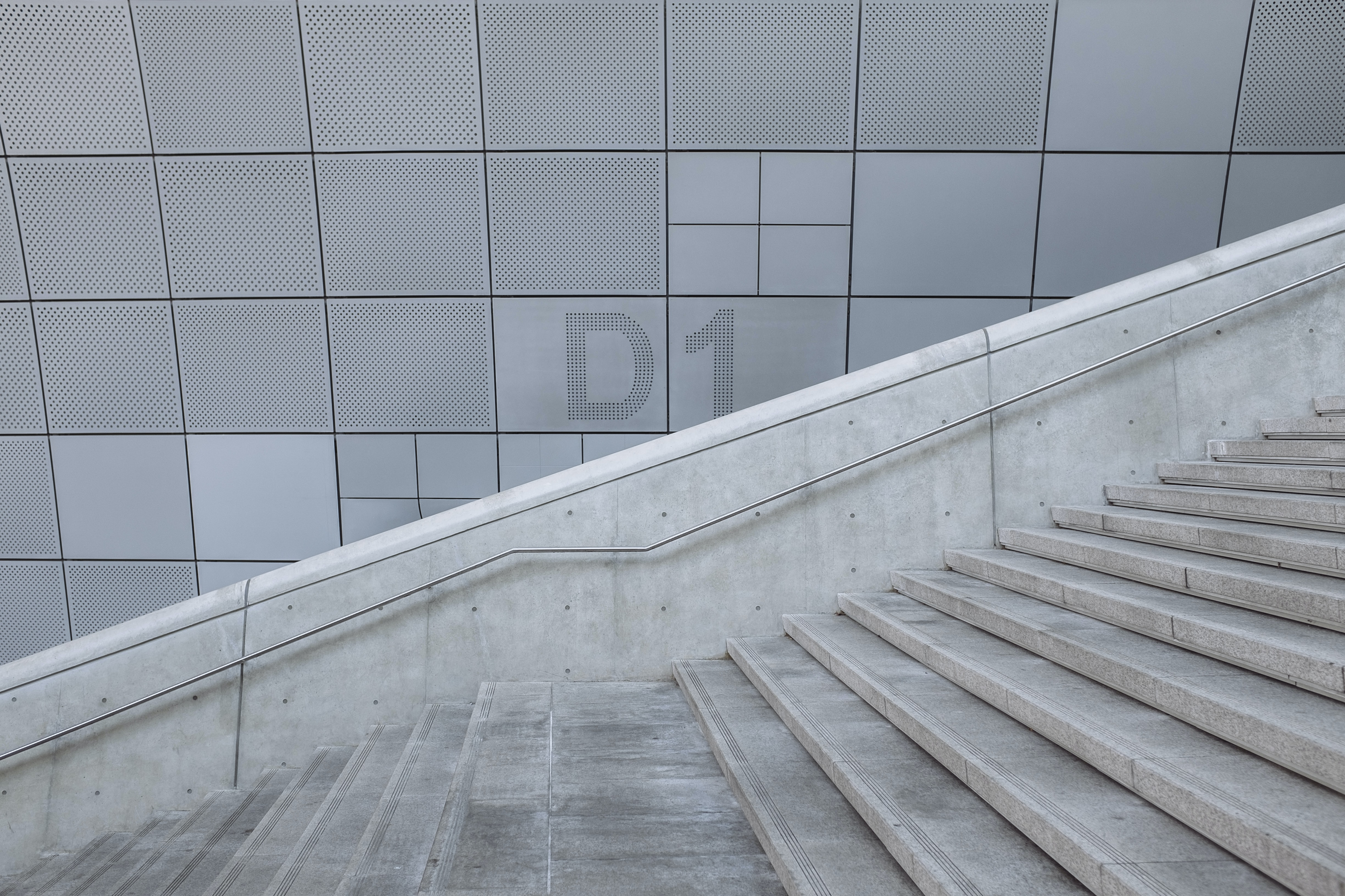 The concrete staircase at level D1 against the gray textured wall.