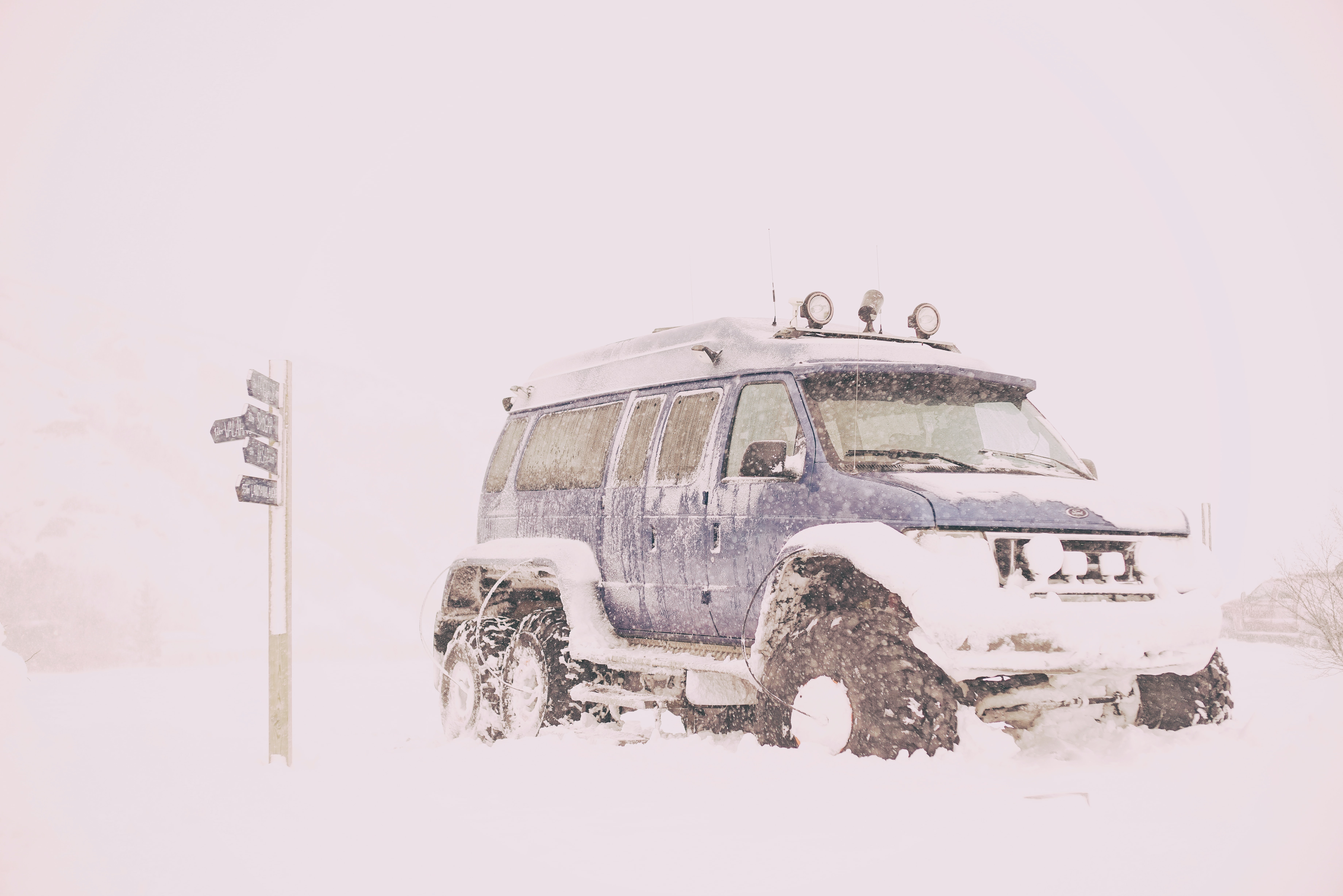 A 4x4 vehicle with flood lights driving through the snow in Iceland