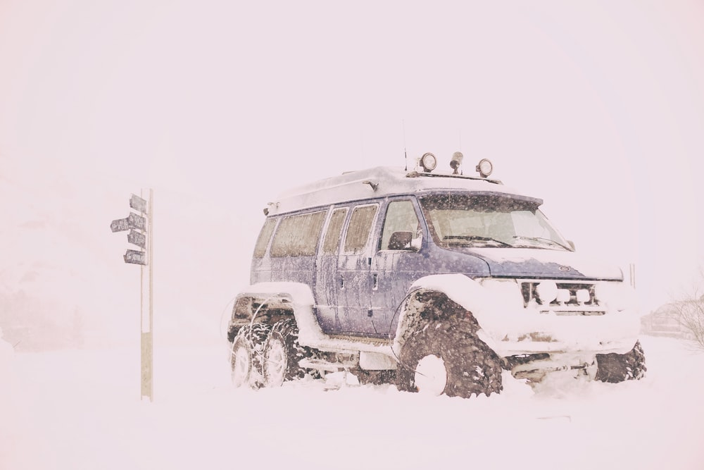 blue SUV covered with snow