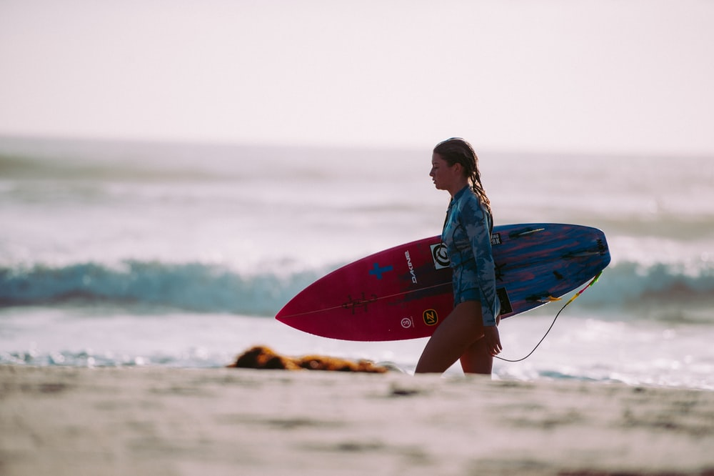 woman carrying red and blue surfboard walking on shore during daytime