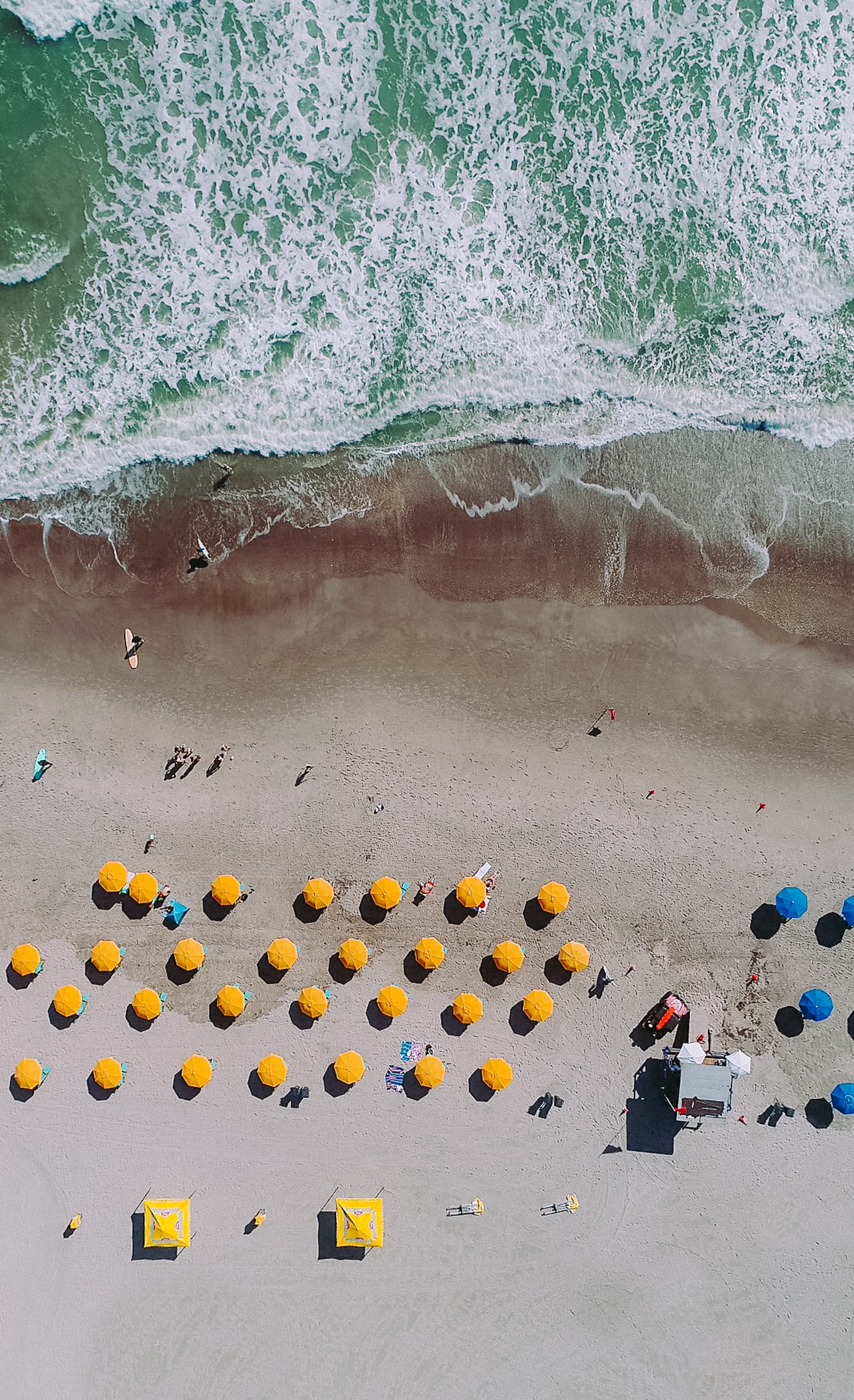 An aerial shot of a sandy beach with rows of yellow and blue umbrellas