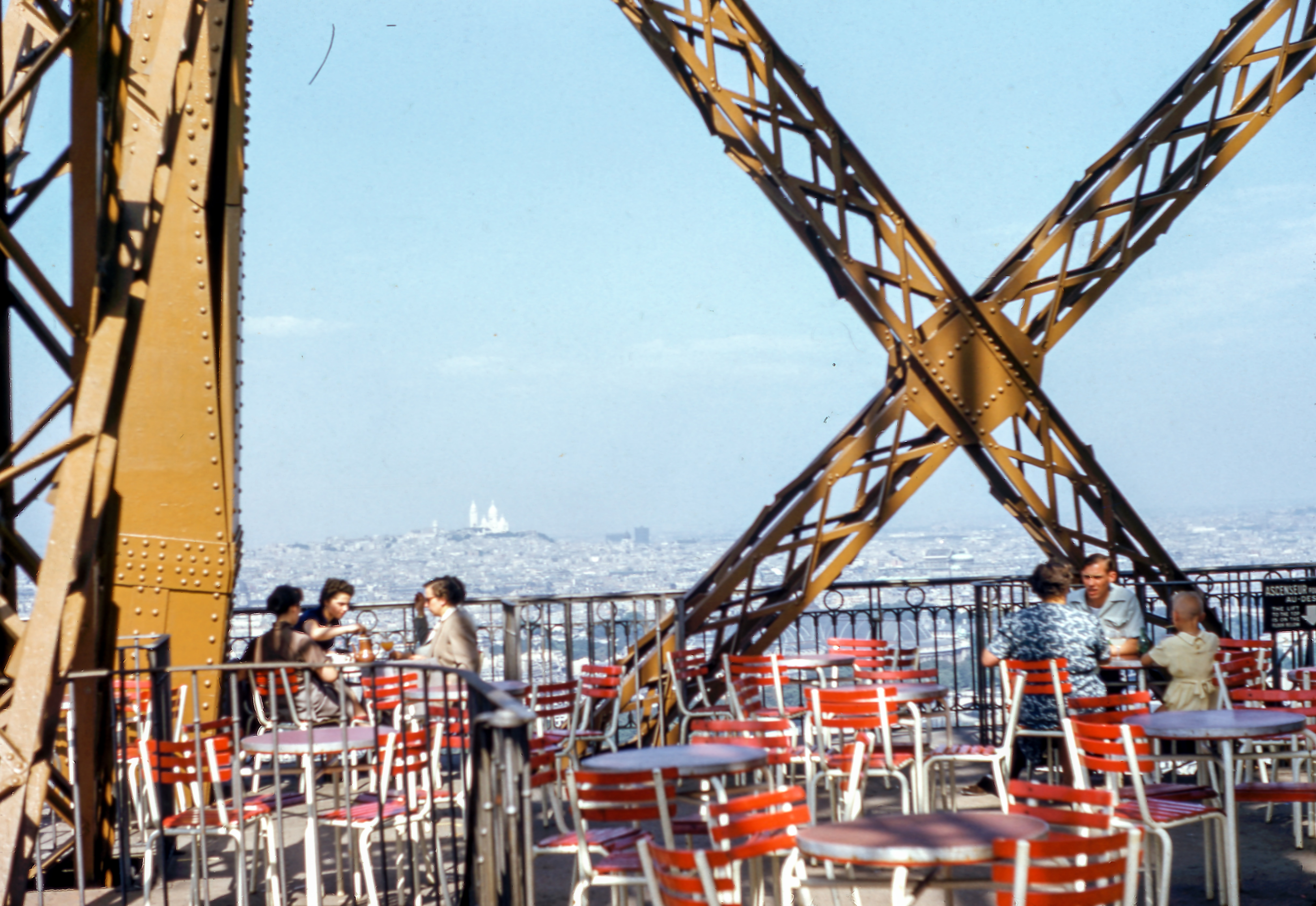 Two groups of people sitting at patio tables on the Eiffel Tower terrasse in Paris