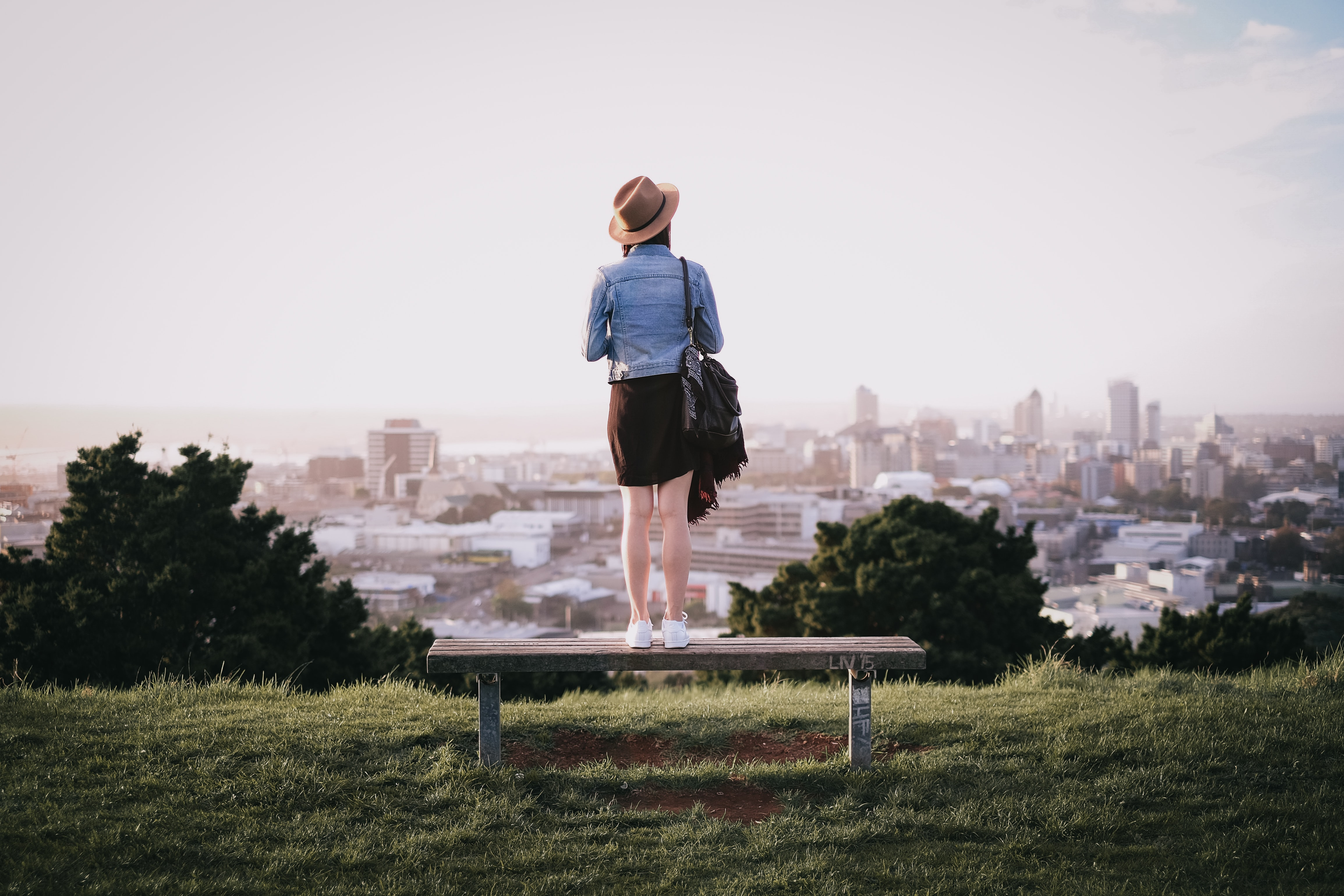 woman standing on bench facing city skyline during daytime