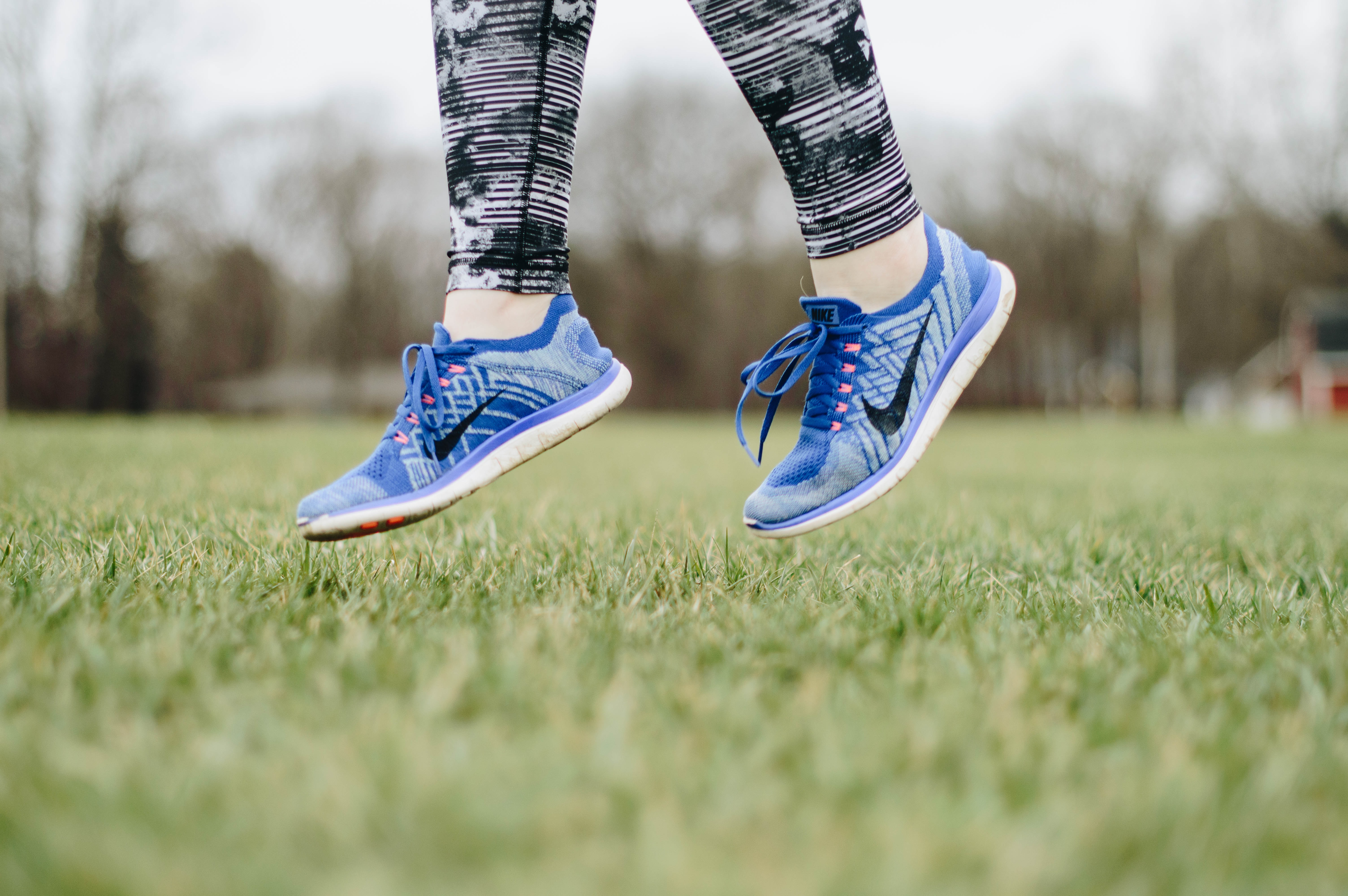 person in blue Nike sneaker jumping