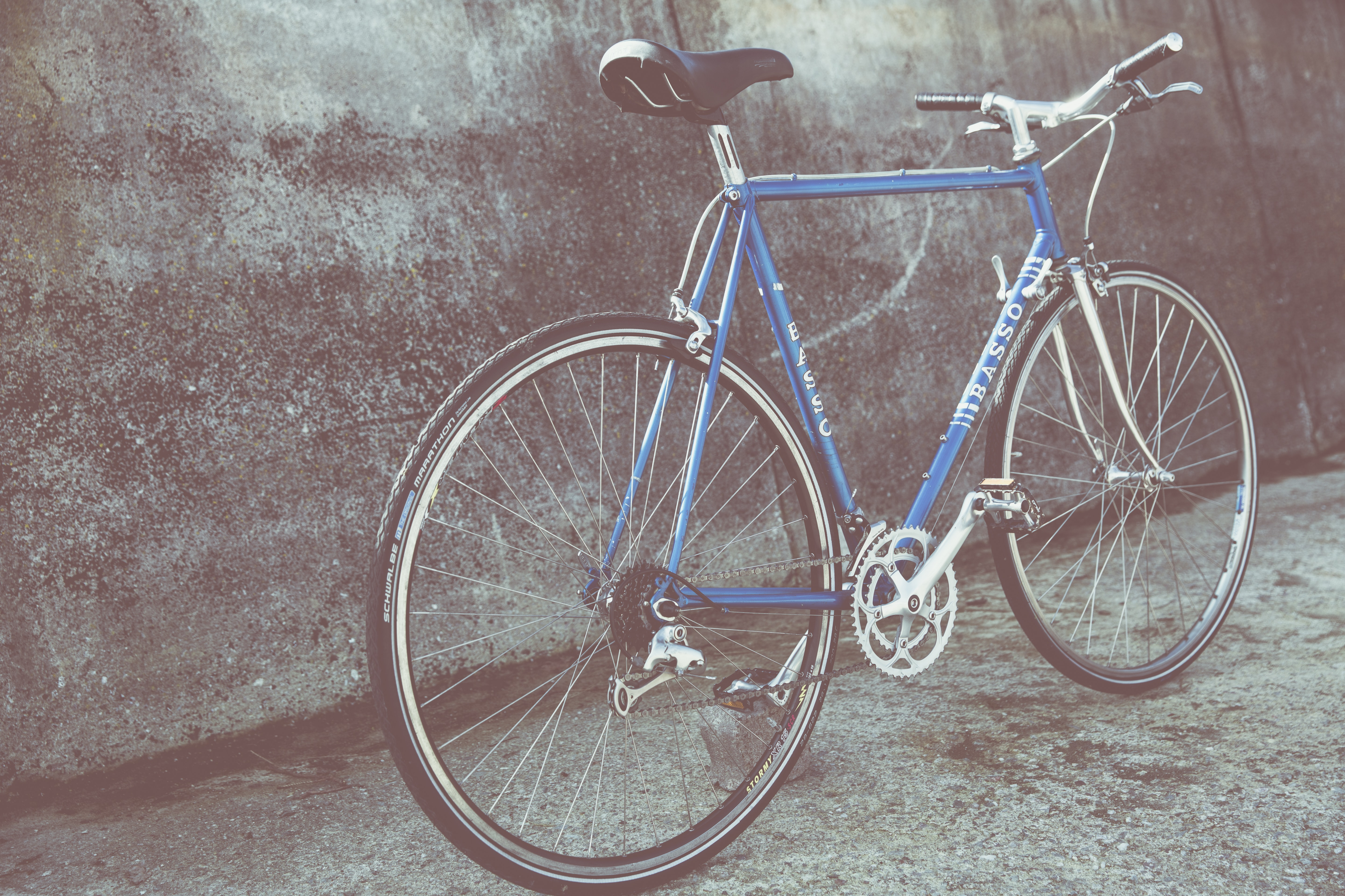blue and gray rigid bicycle parked beside wall