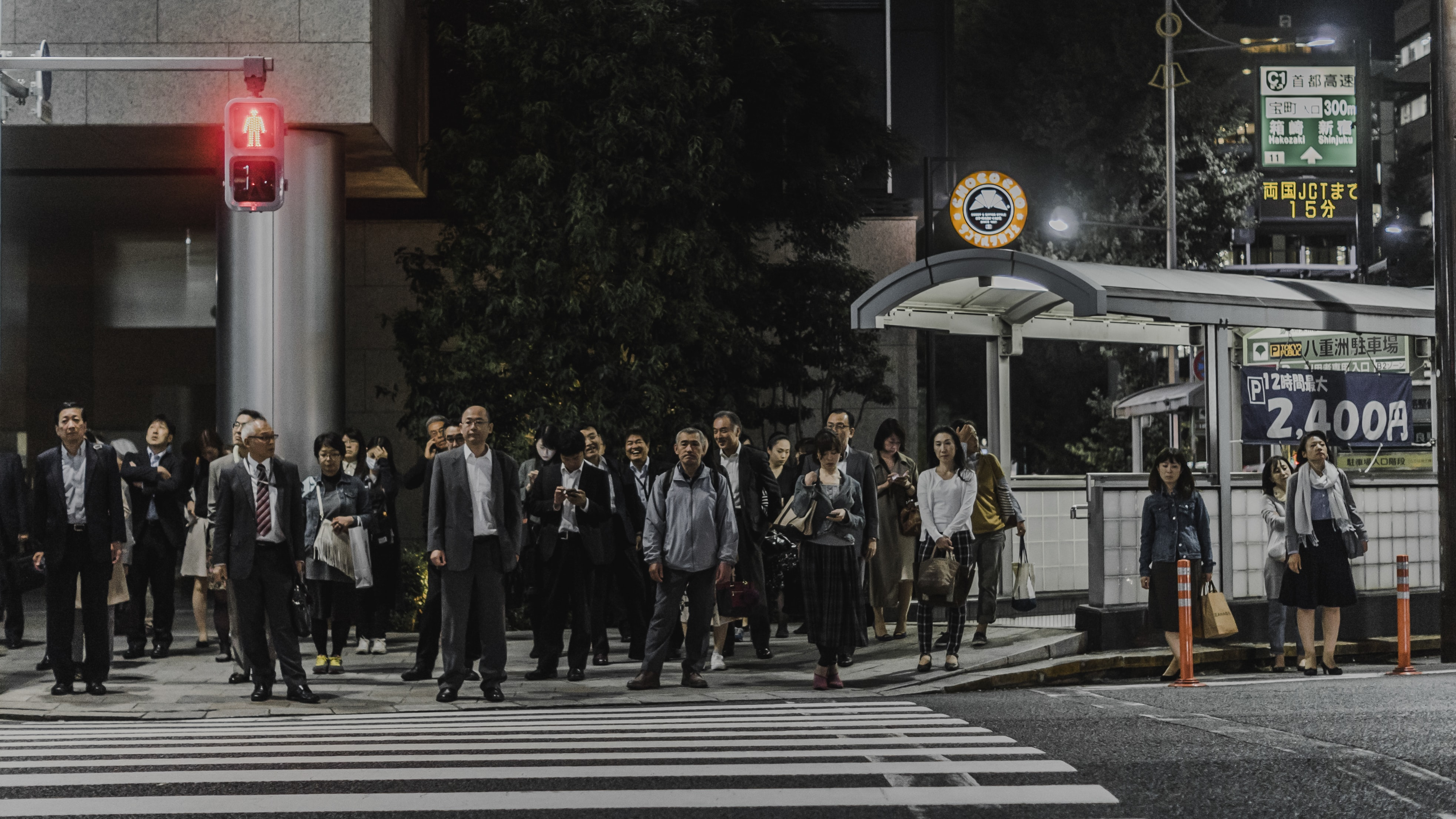 Pedestrians are waiting for the lights to turn green at the crosswalk in Tokyo.