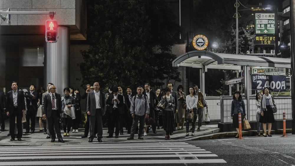 people standing in front of pedestrian lane during daytime
