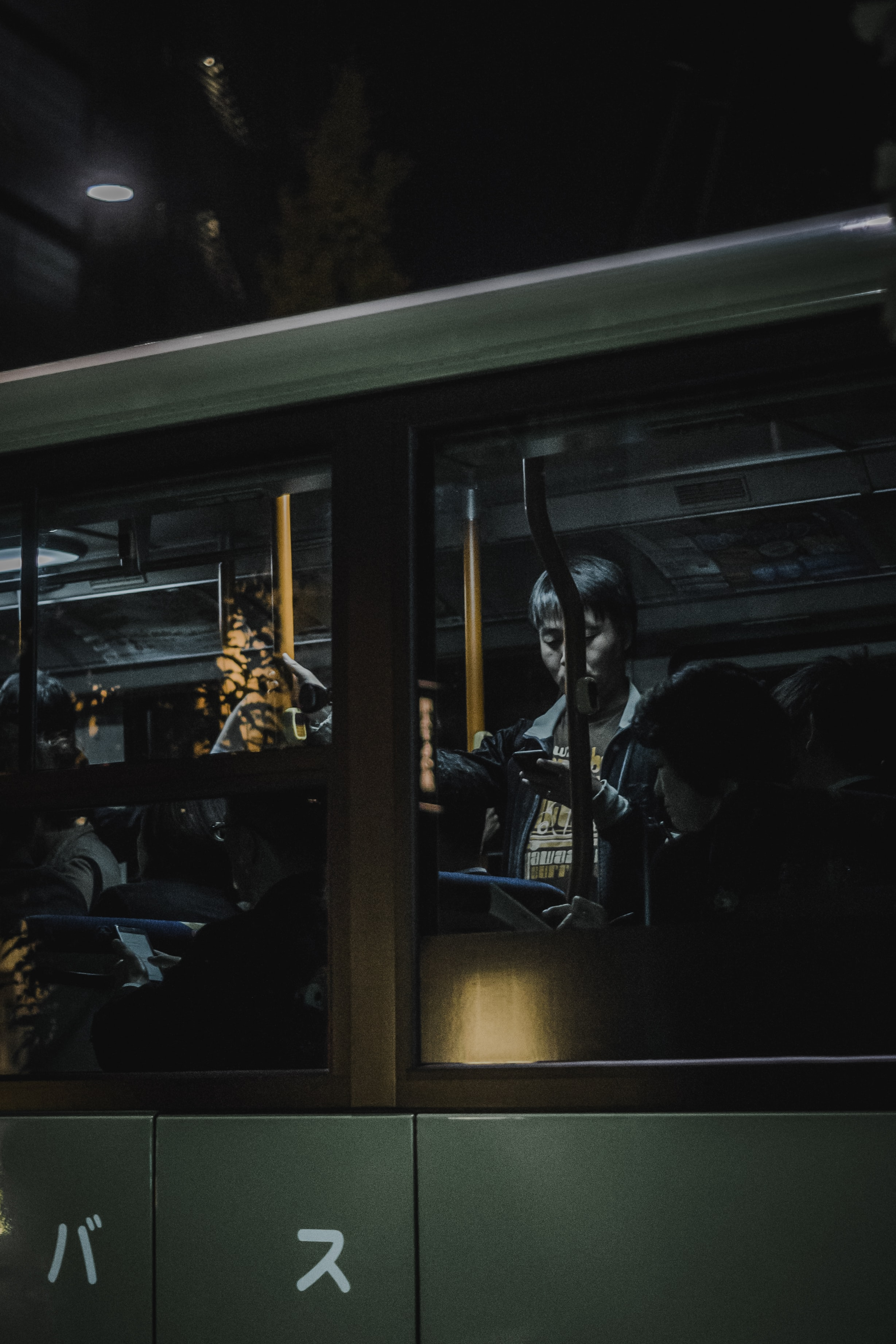 A man using a phone seen through the window of a bus driving by