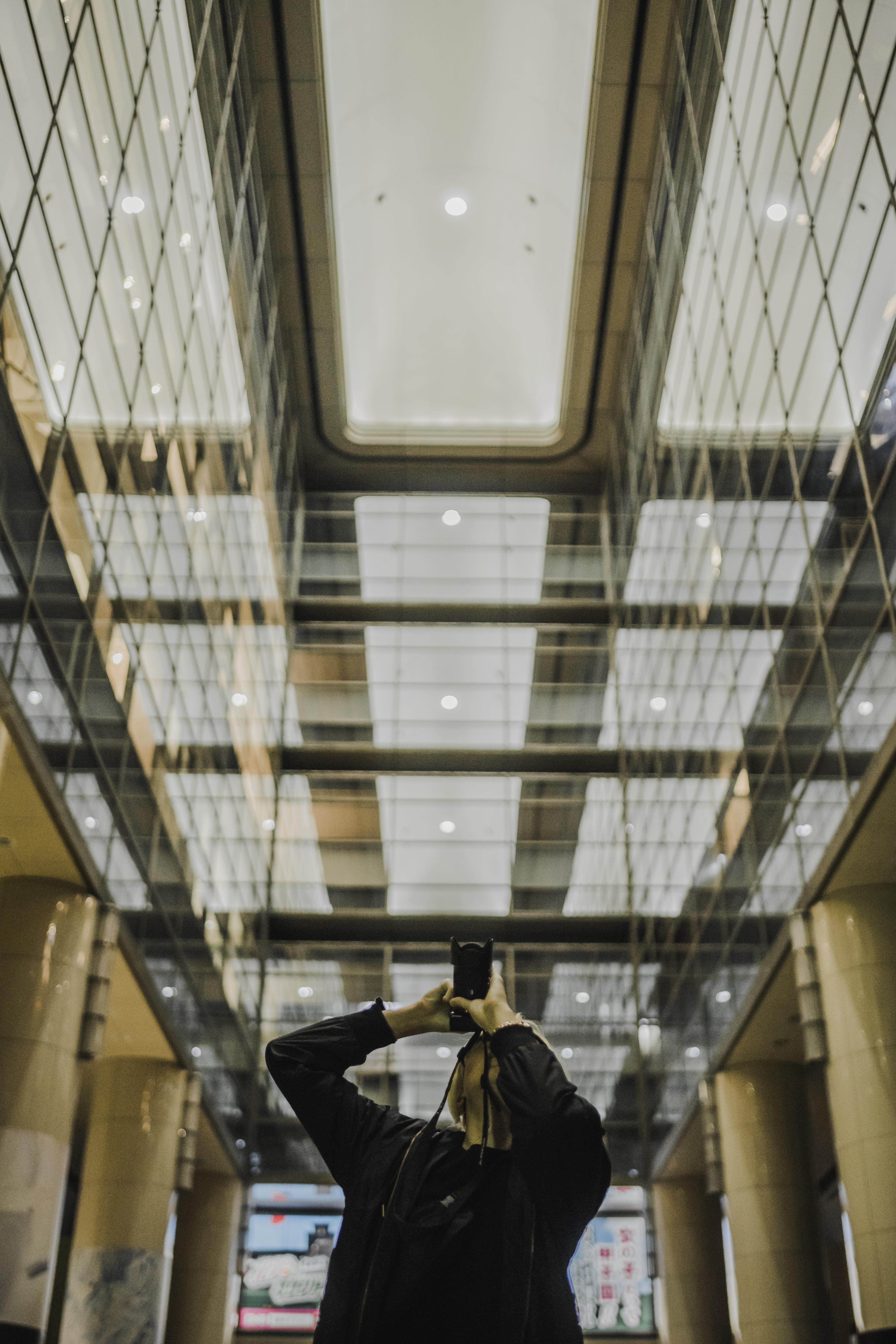 man holding DSLR camera while taking photo in hallway