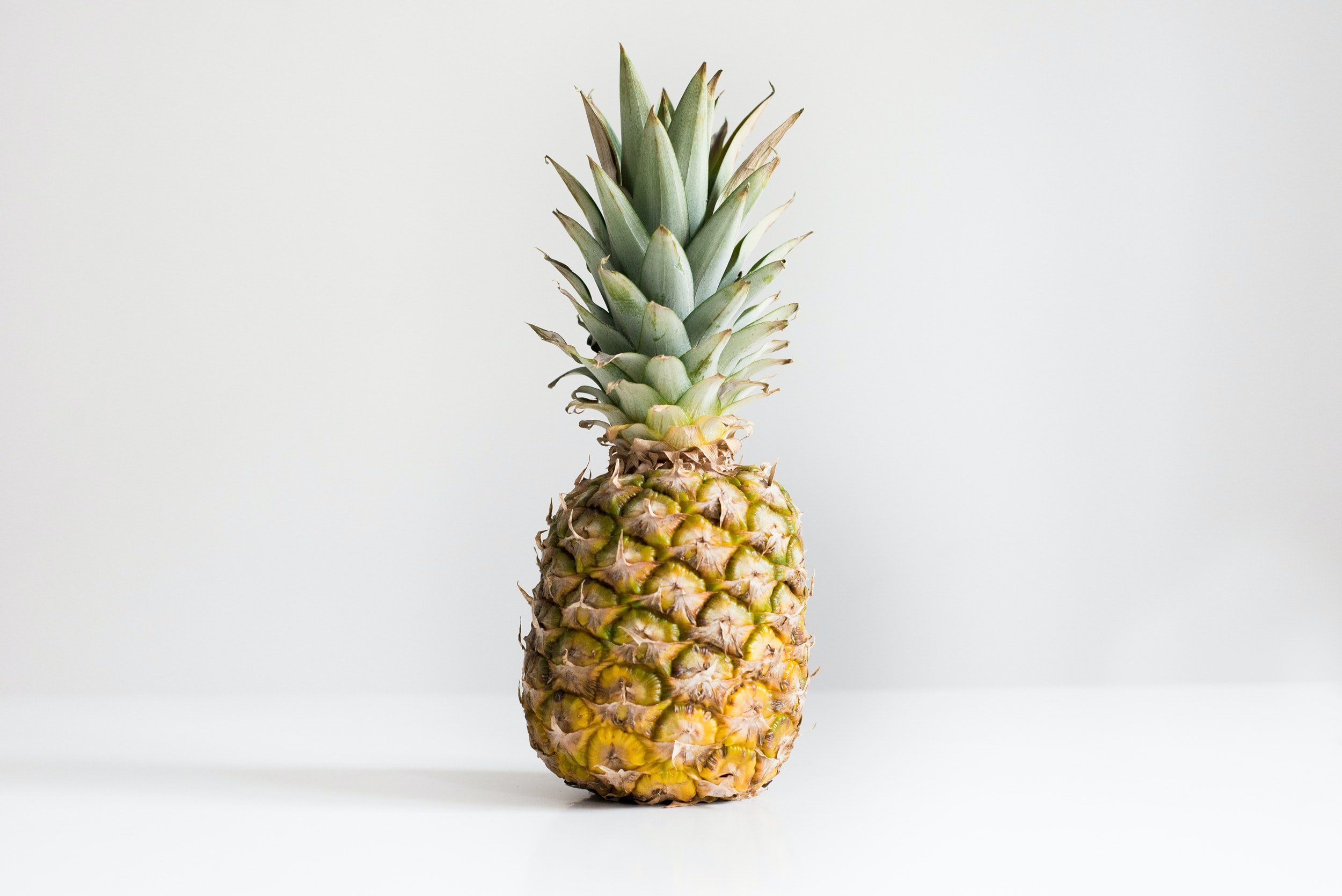 One pineapple with green top on a white background