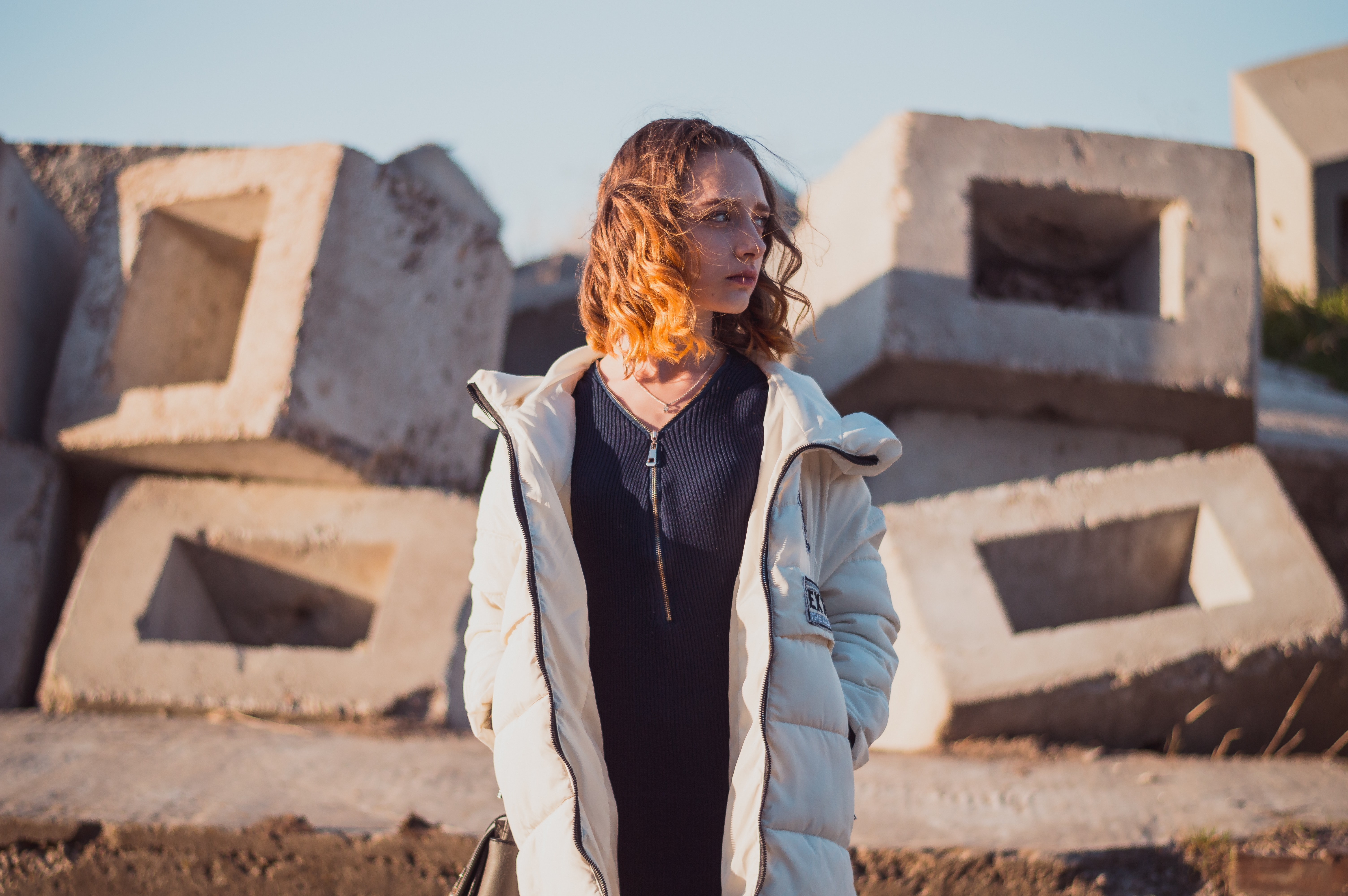 Woman in an unzipped winter jacket by construction cinder blocks