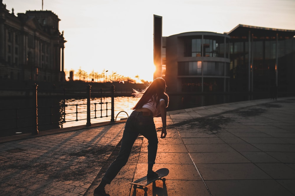 woman playing skateboard near river during daytime