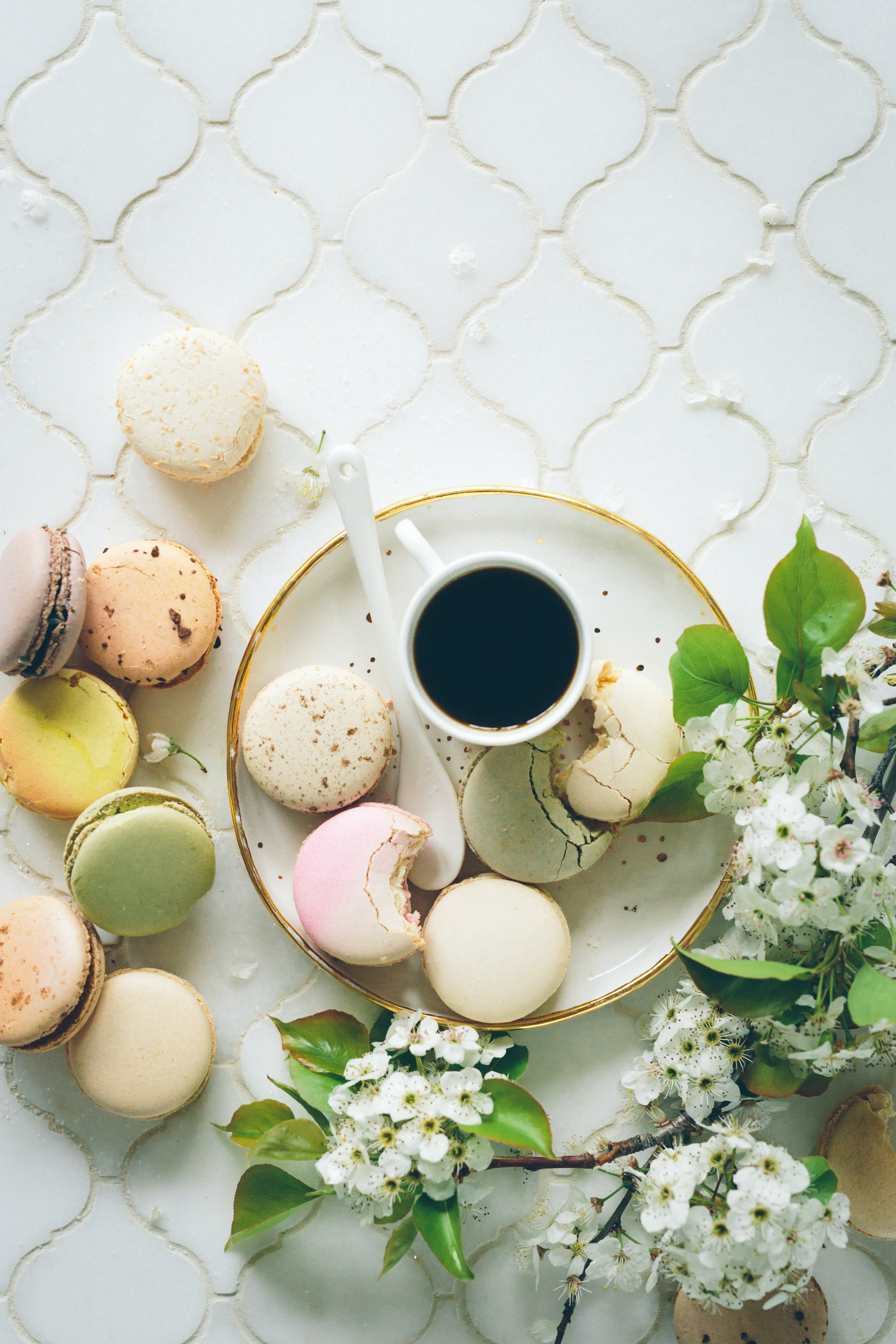 An overhead shot of a cup of coffee and macaroons on a coaster next to white flowers