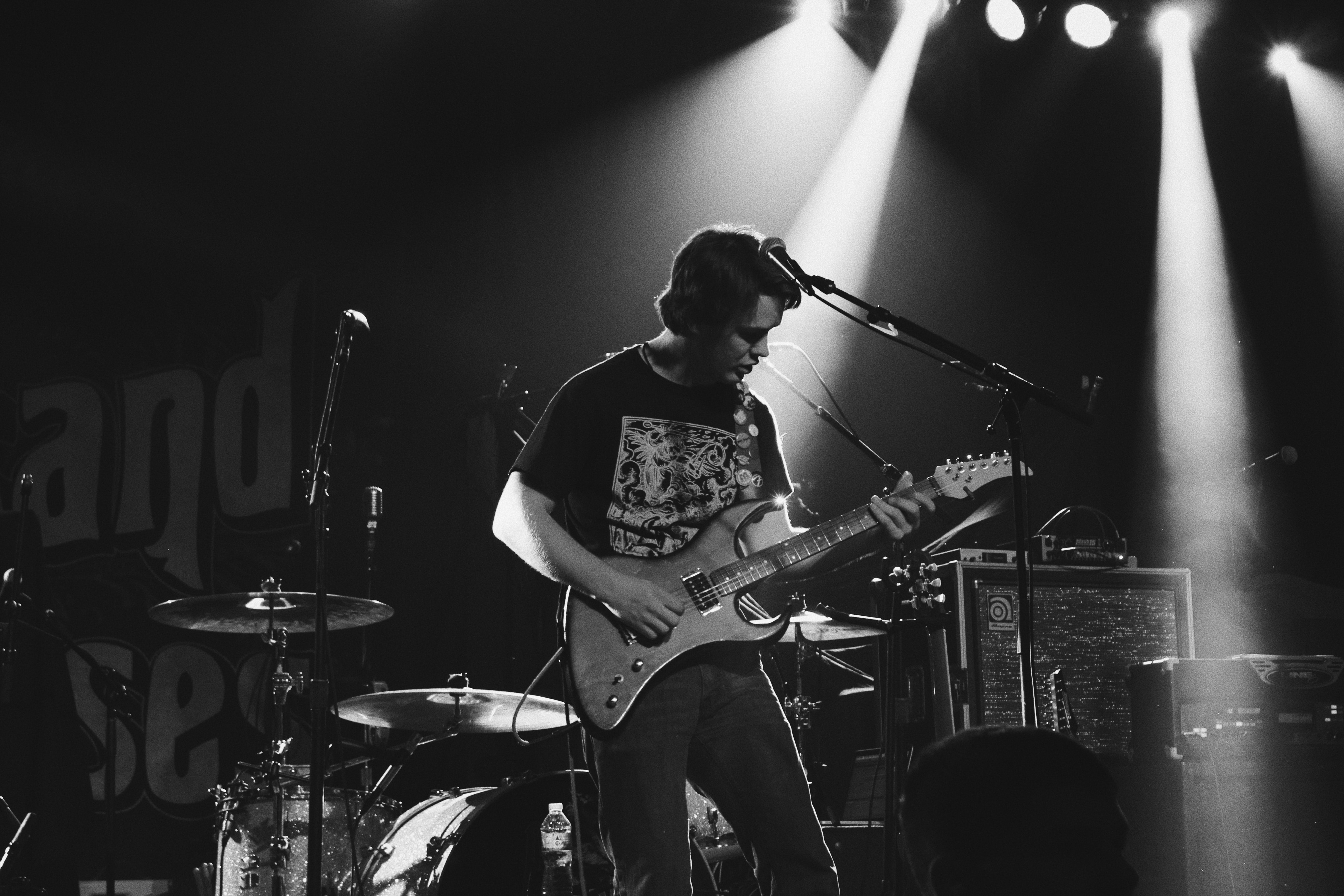 A black-and-white shot of a man playing an electric guitar on a busy stage