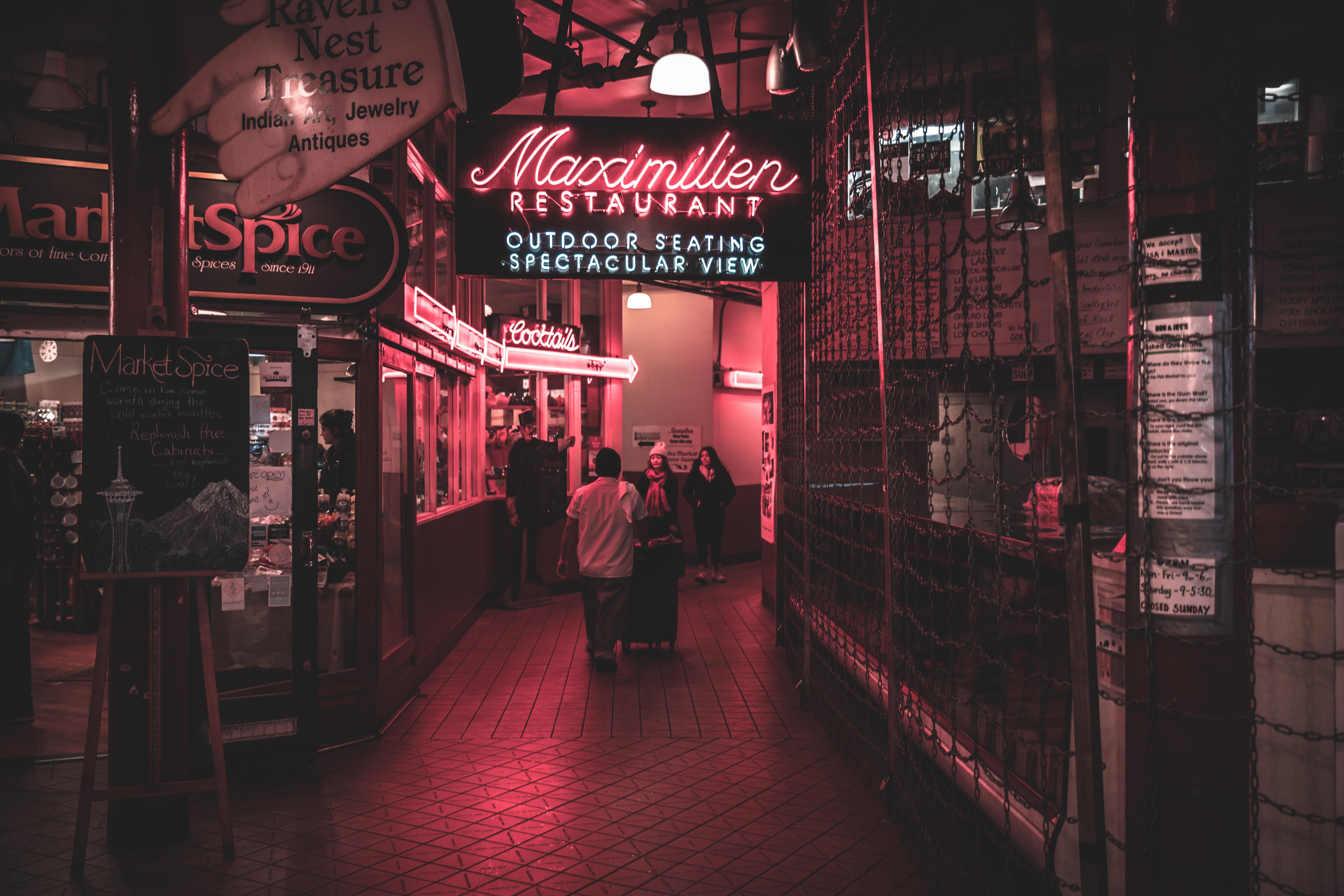 Red neon restaurant signs glow inside a Seattle market