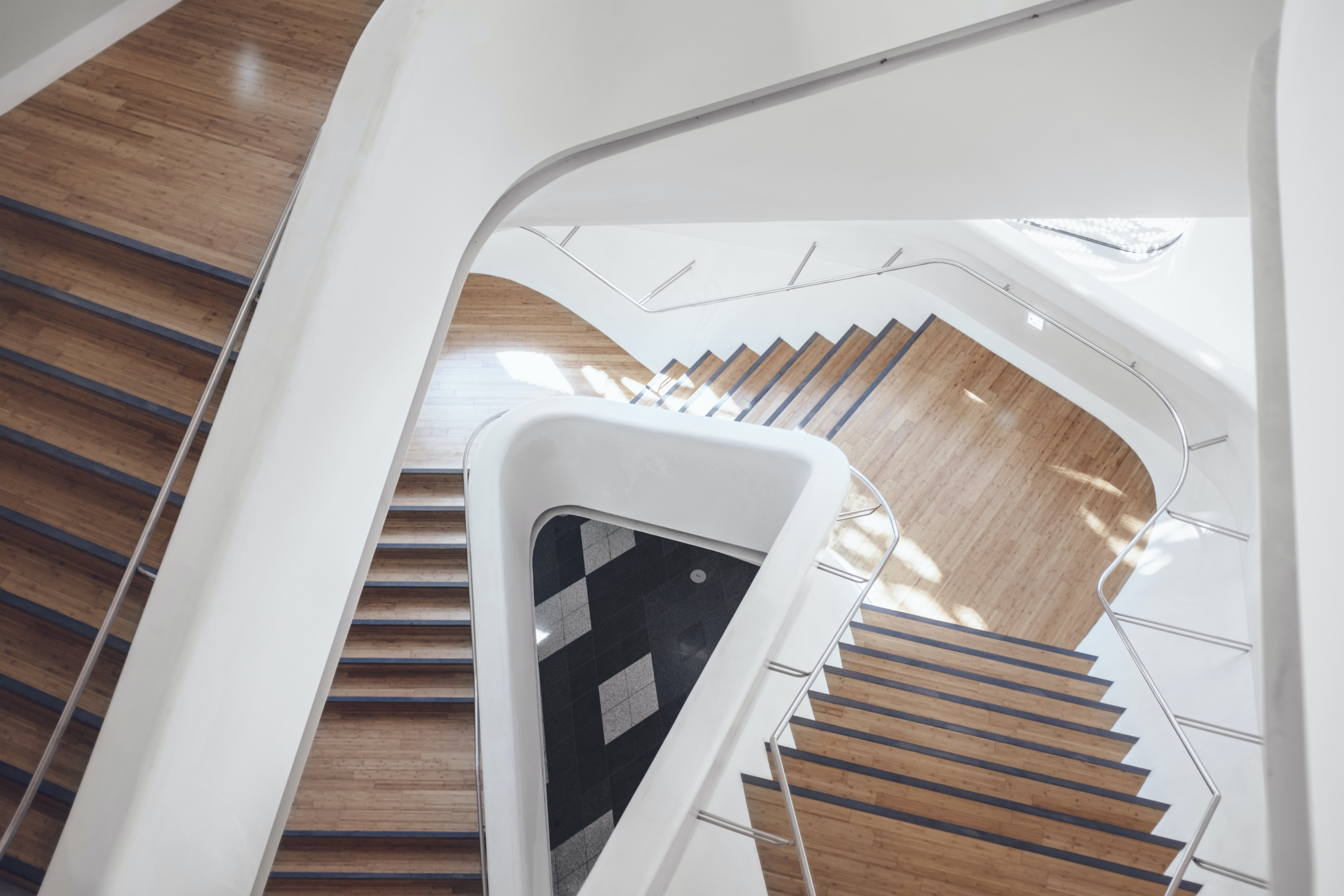 View down a white-painted stairway with wooden steps