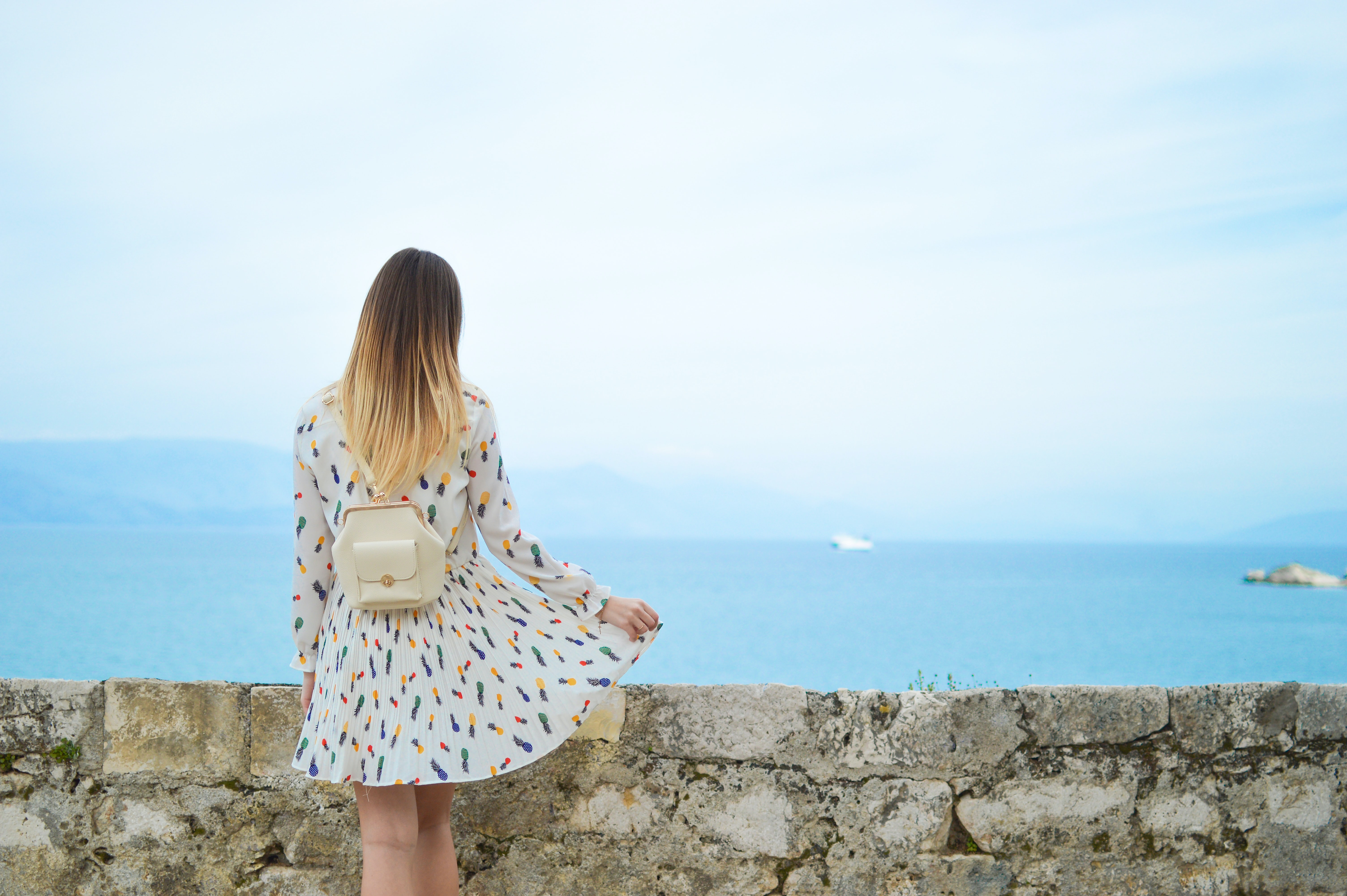 woman in white dress looking at body of water