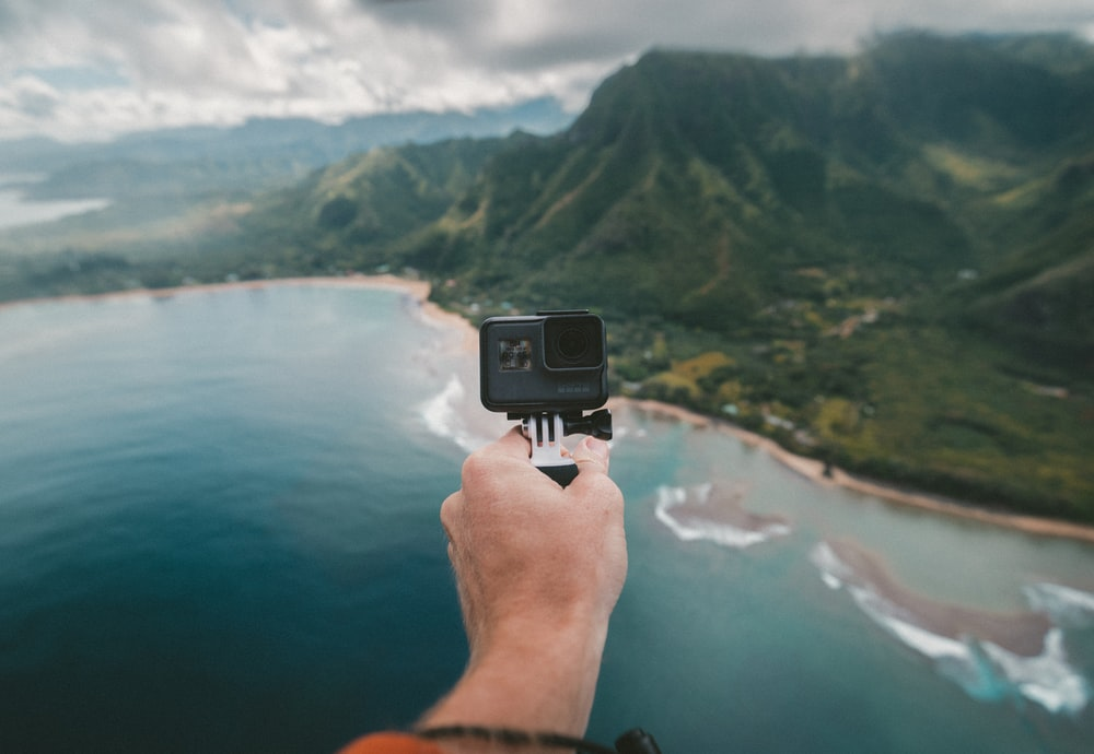 person holding black action camera fronting green mountains