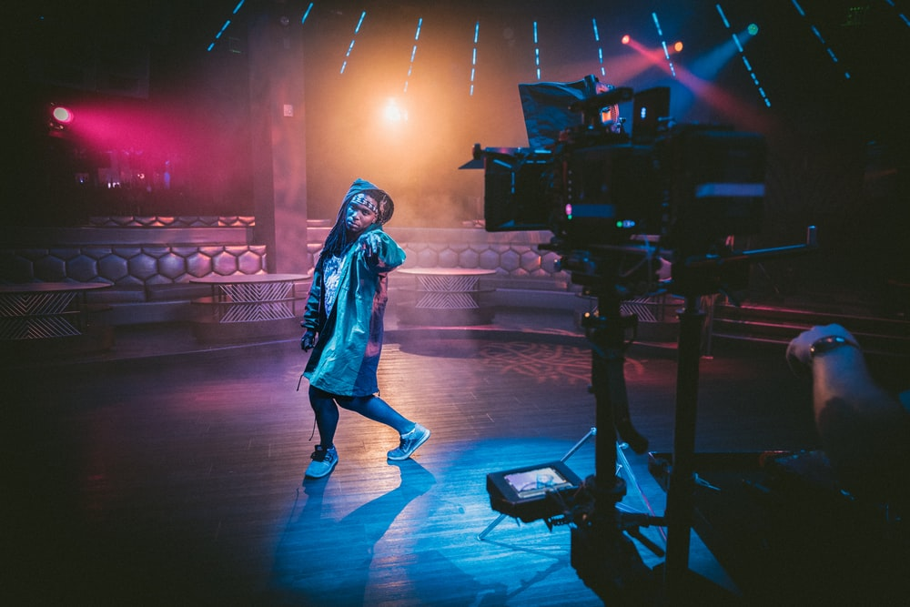 woman dancing on stage near black cameras
