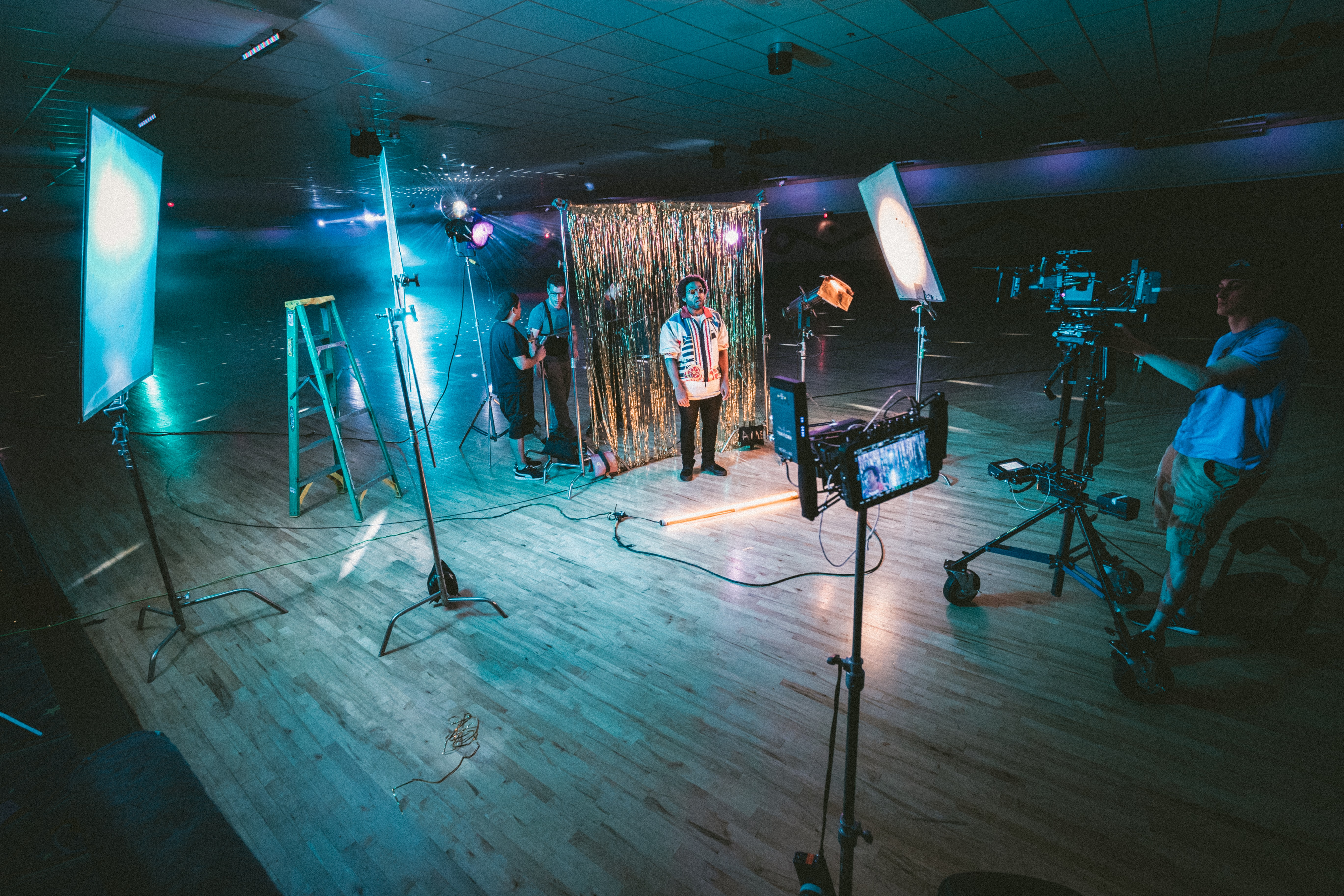 man standing in front of cameras with string lights background