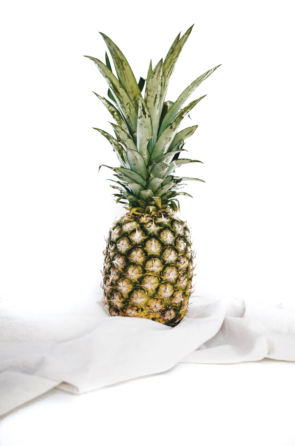 yellow and green pineapple fruit on white textile