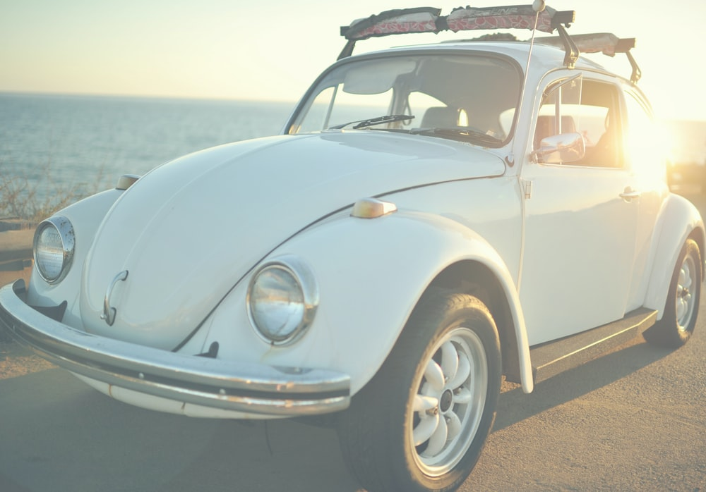 white Volkswagen Beetle on road at daytime