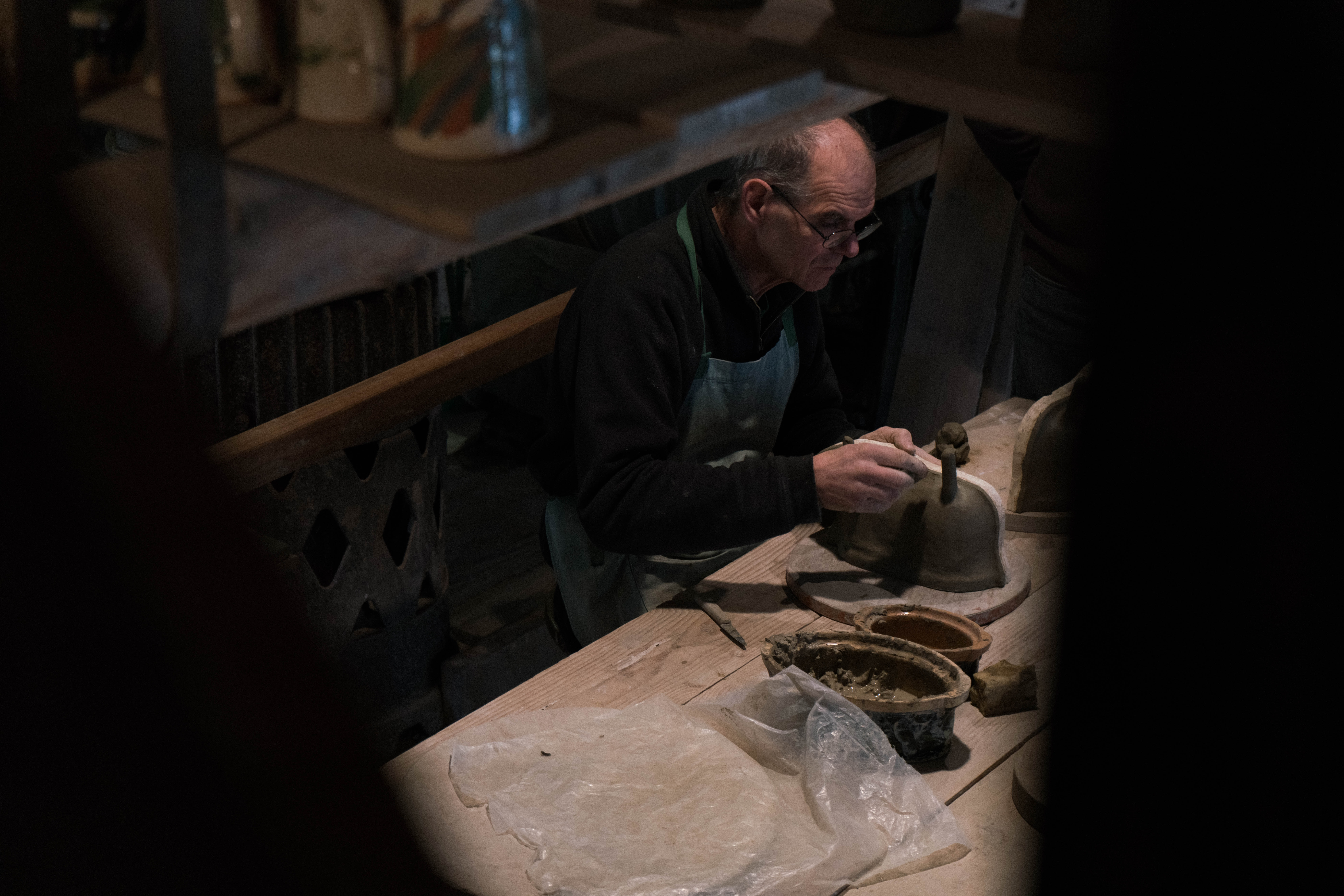 An elderly man working with clay and wood at a workbench