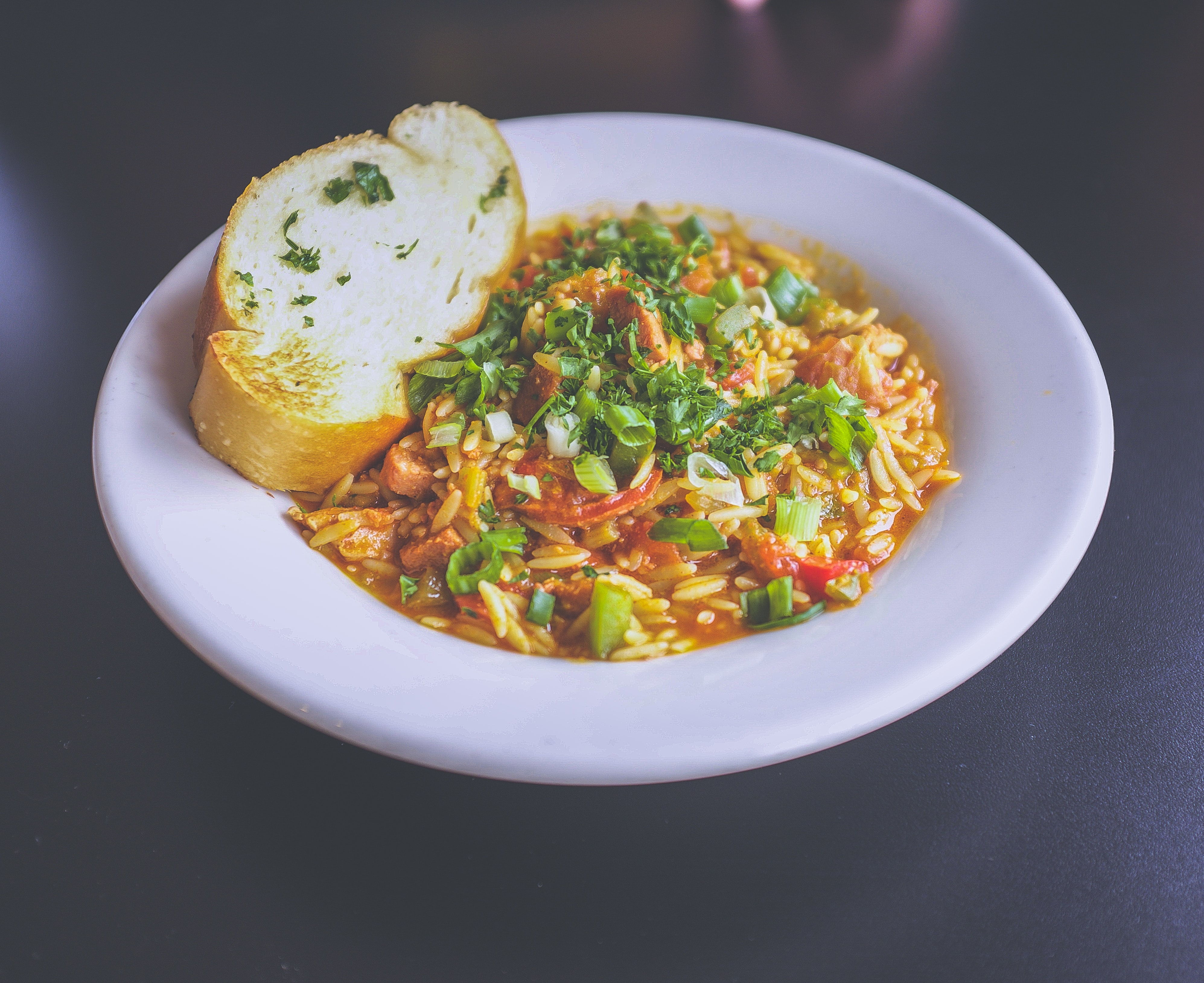 Rice pasta dish garnished with green onions and parsley with a slice of garlic bread served in a ceramic bowl