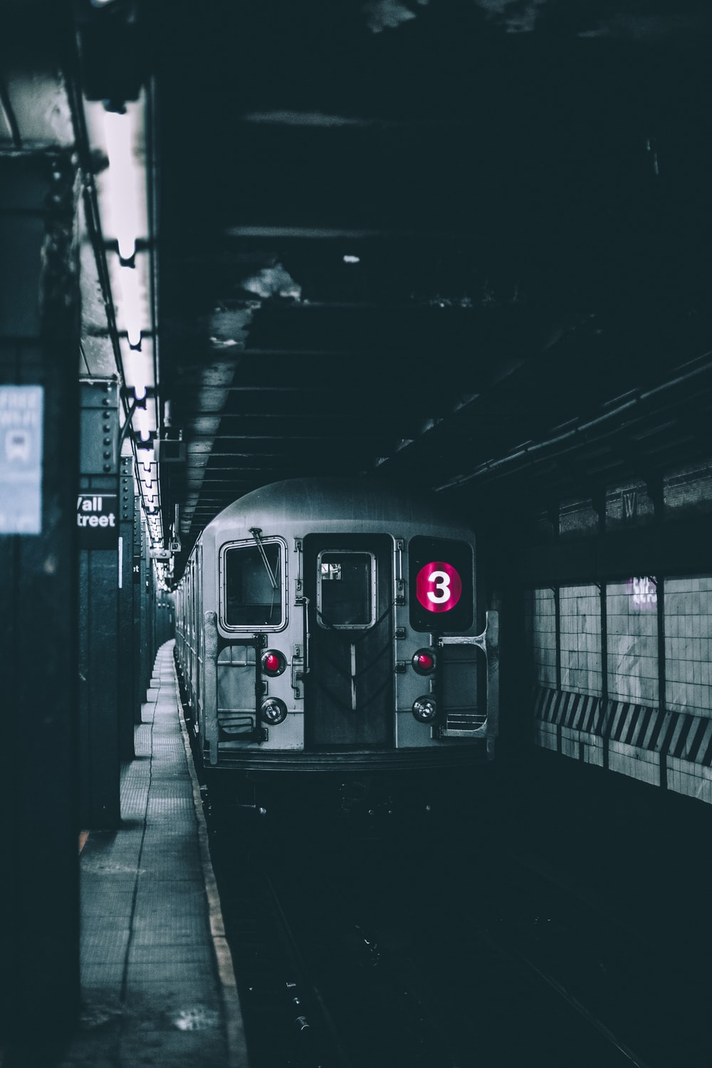 selective color photo of a subway station with train