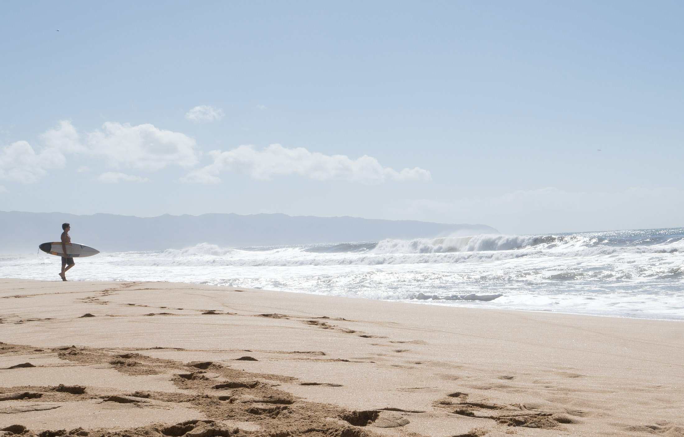 Surfer on the sand beach in O'ahu walking towards rough ocean