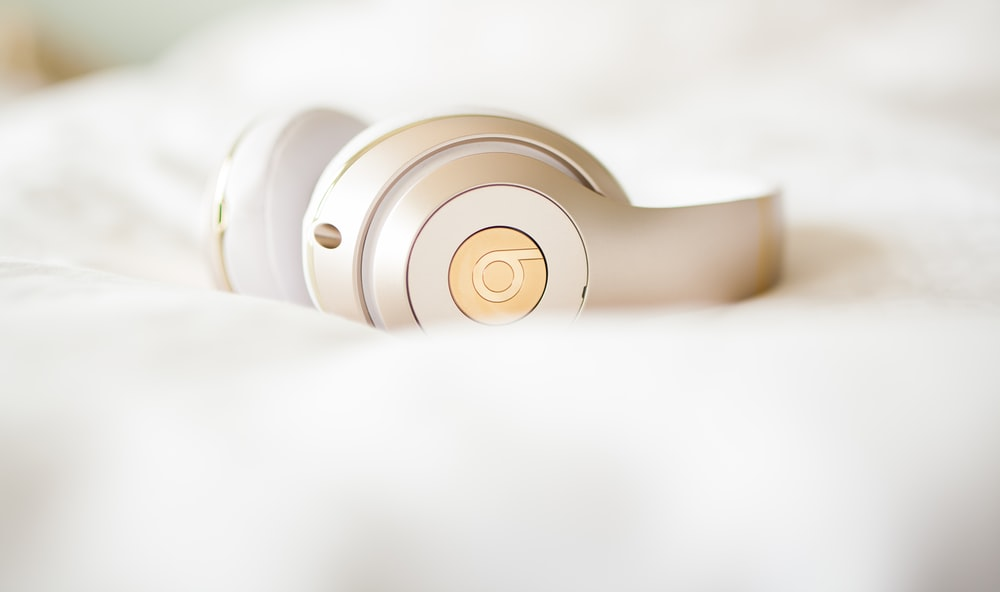 gold edition Beats by Dr.Dre wireless headphones on top of white textile