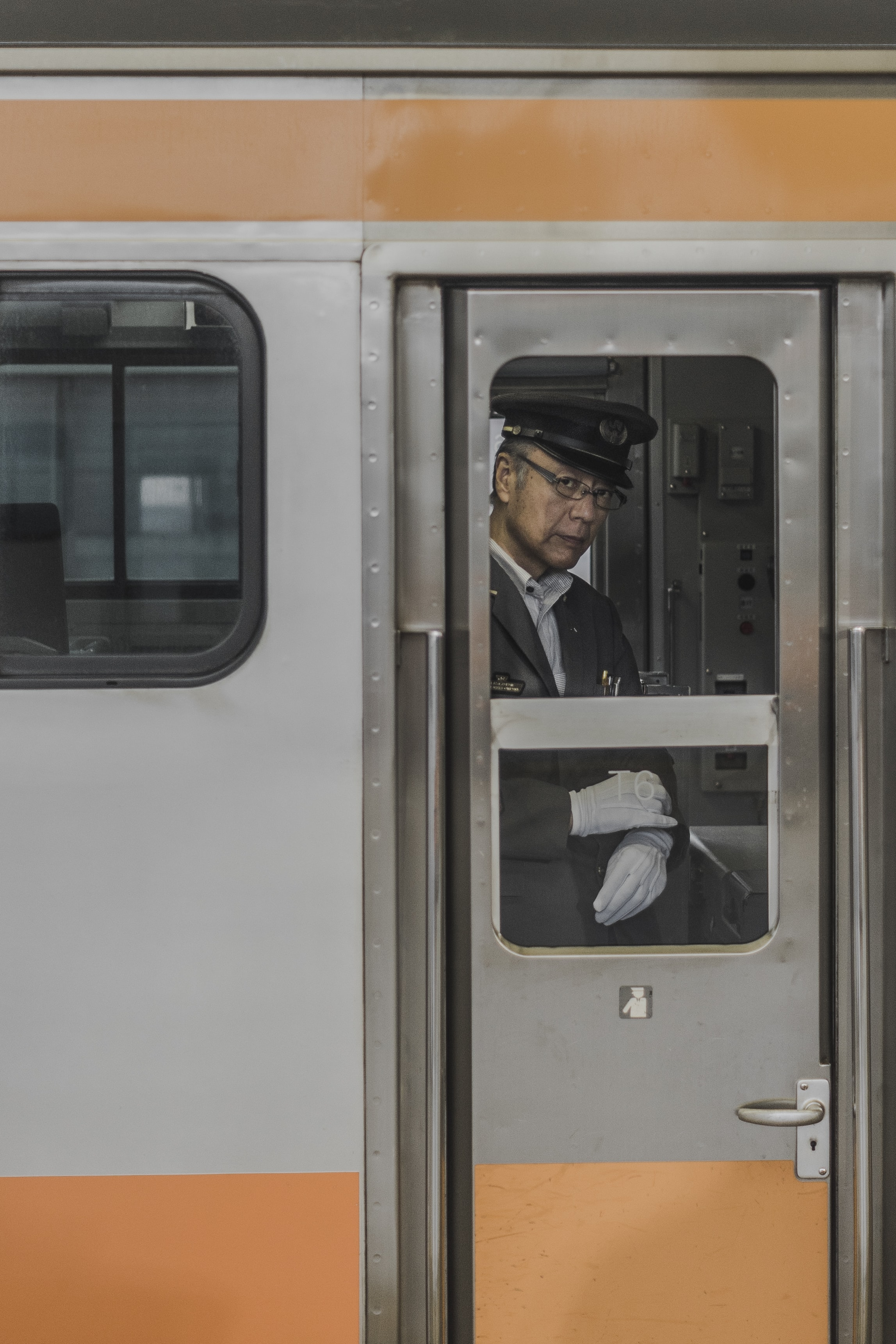 A male train conductor with white gloves in one of the subway trains in Tokyo.