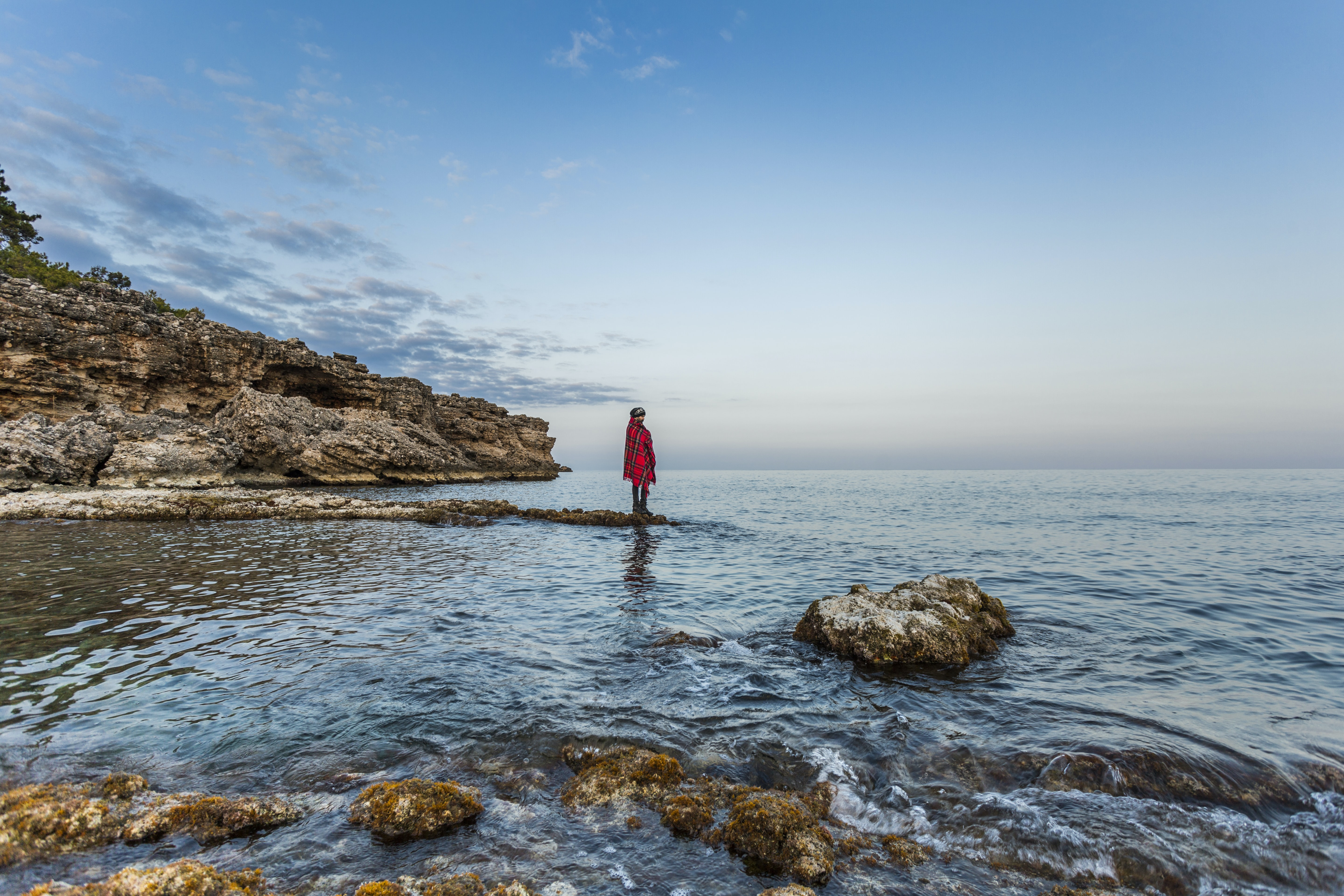 person standing on rock beside body of water during daytime