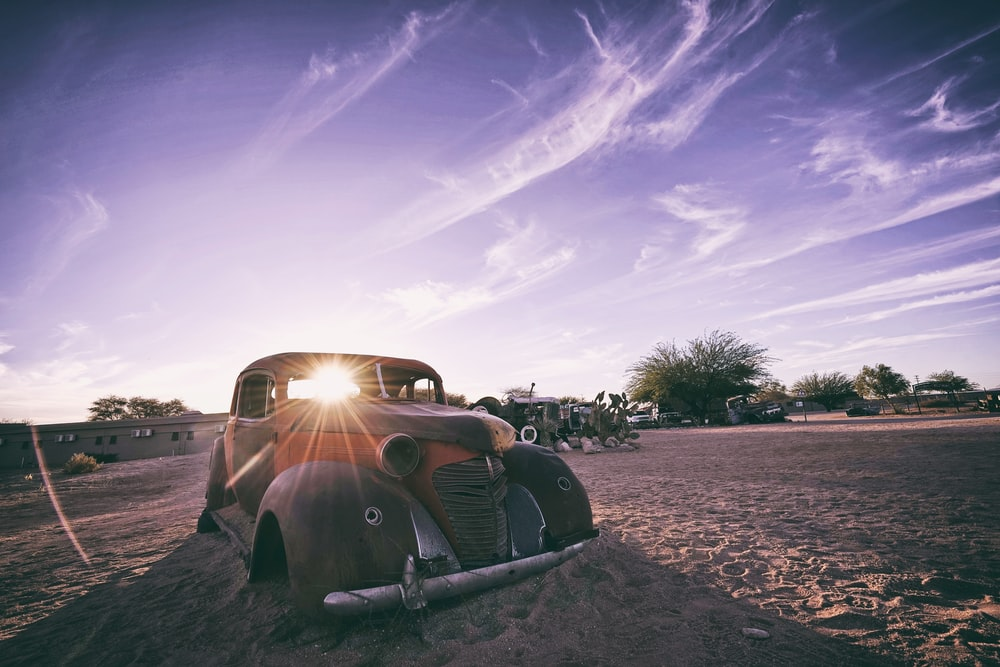 brown vehicle on sand during daytime