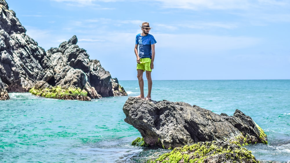 man in blue t-shirt standing on gray rock on see