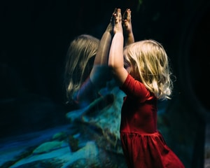 girl leaning on glass fish tank raising her two hands