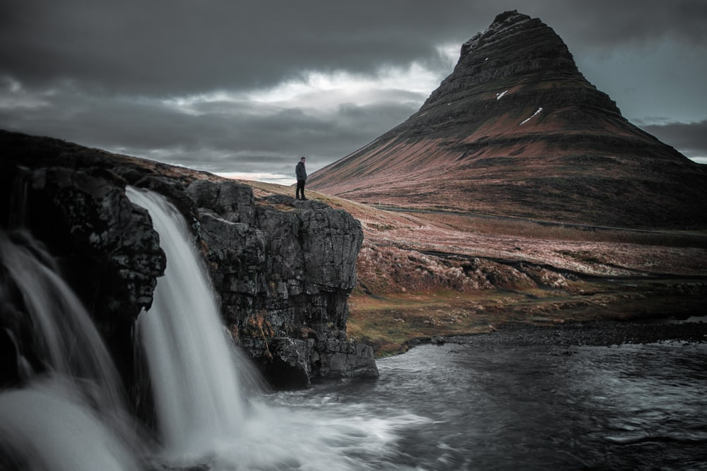 photography of man standing of top of mountain
