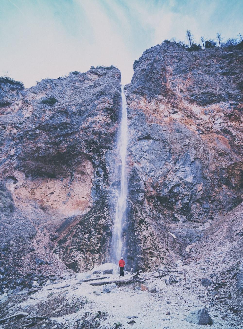 person wearing red jacket standing near waterfalls