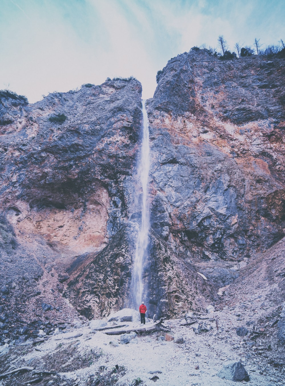 person wearing red jacket standing near waterfalls