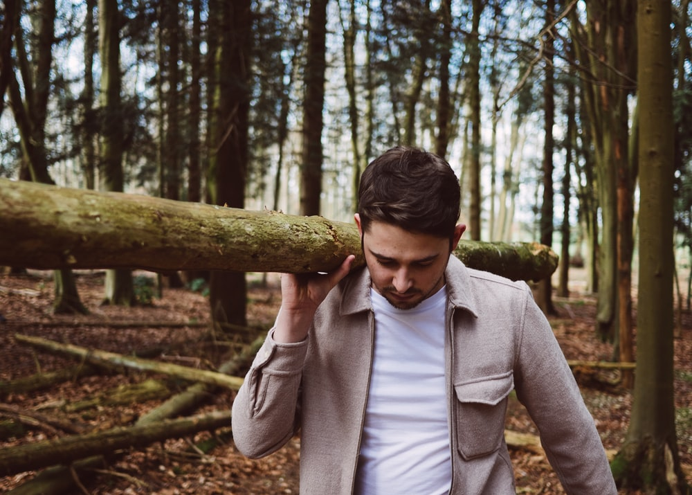 man carrying wood log