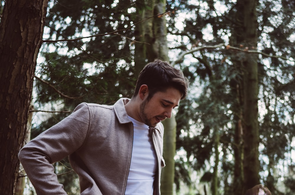 man standing beside trees during daytime