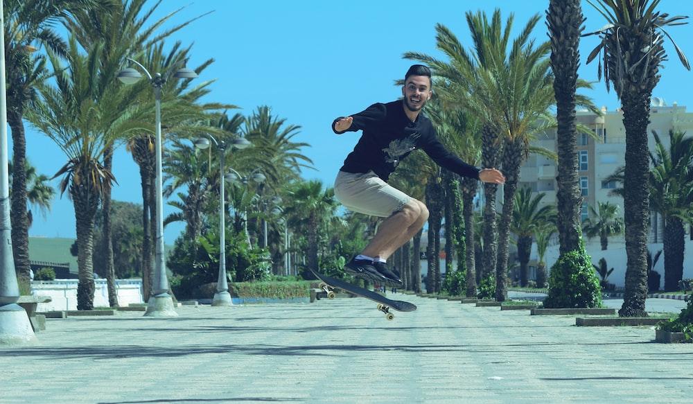 man in black jacket and black pants riding skateboard during daytime