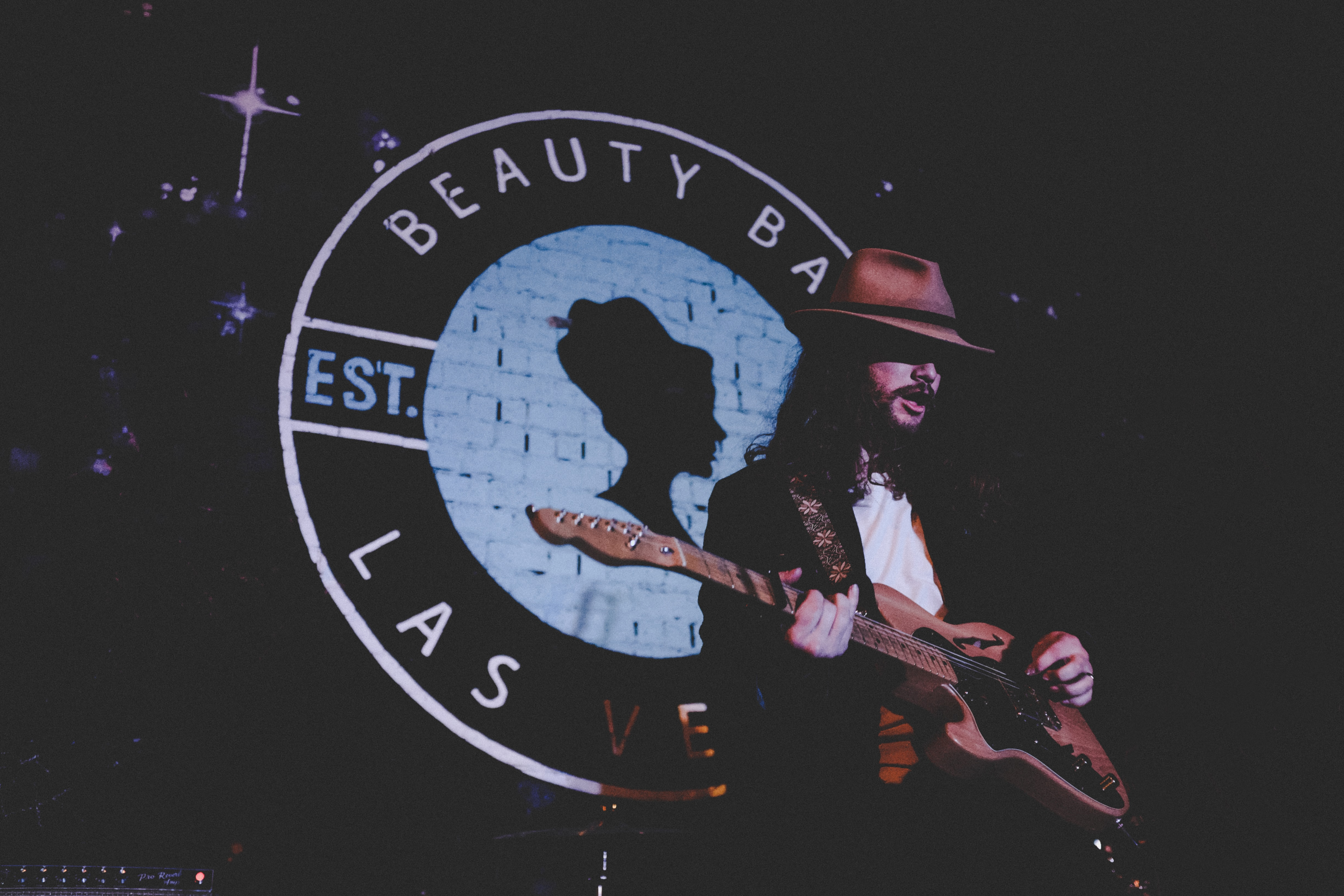 A flamboyant man playing a guitar in front of a Beauty Bar Las Vegas logo