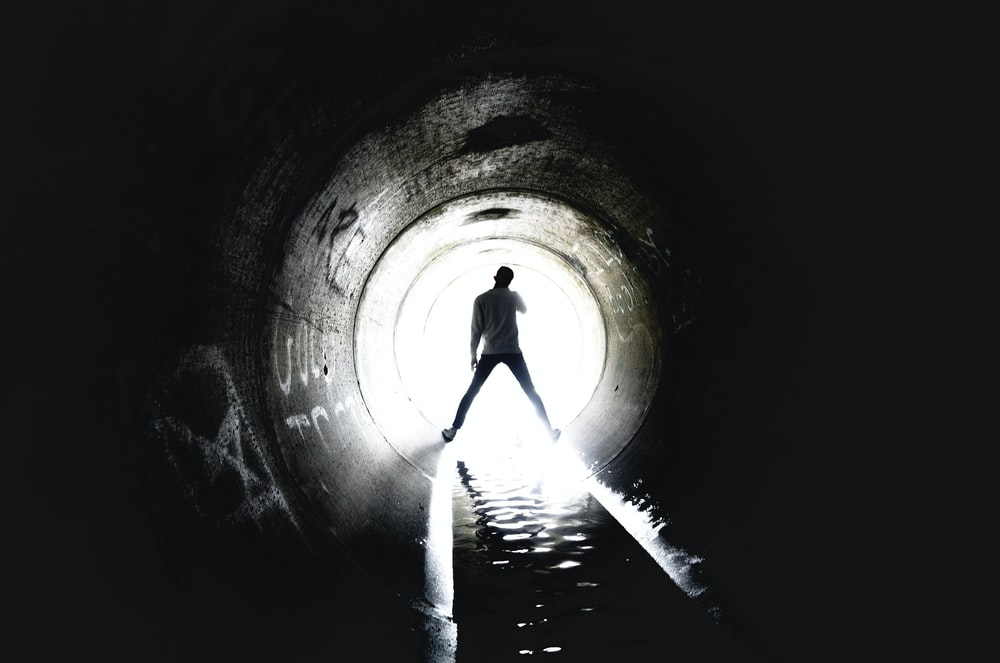 person standing inside sewer tunnel