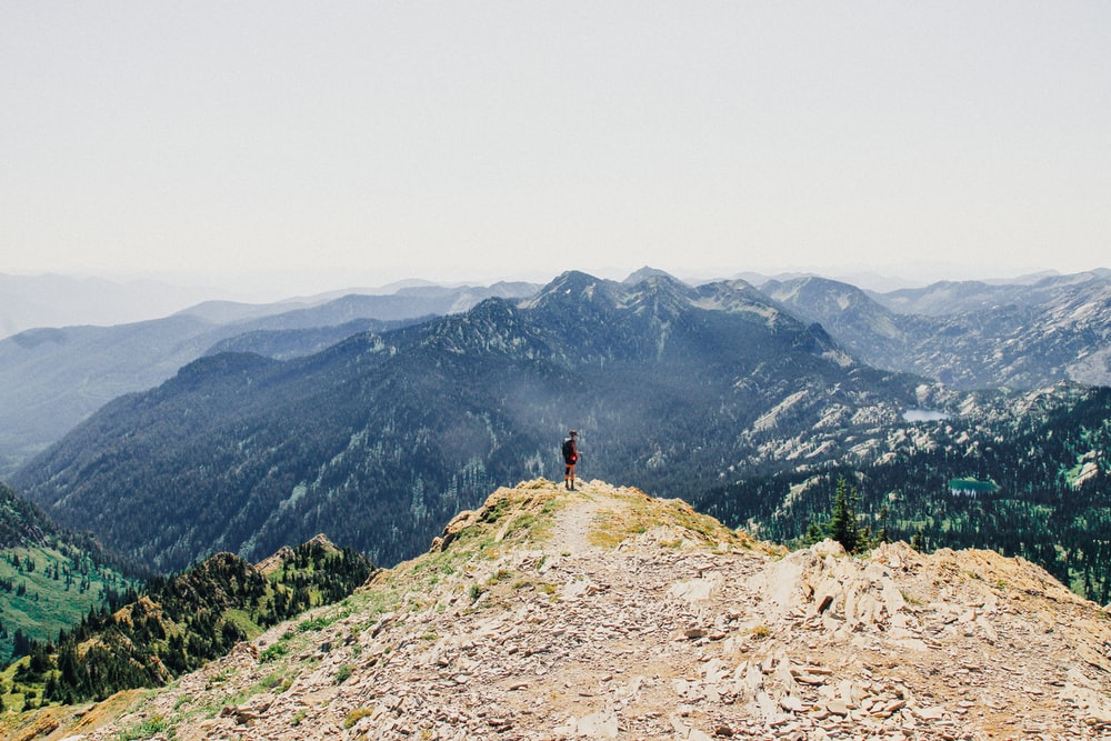 person standing on mountain cliff under white sky