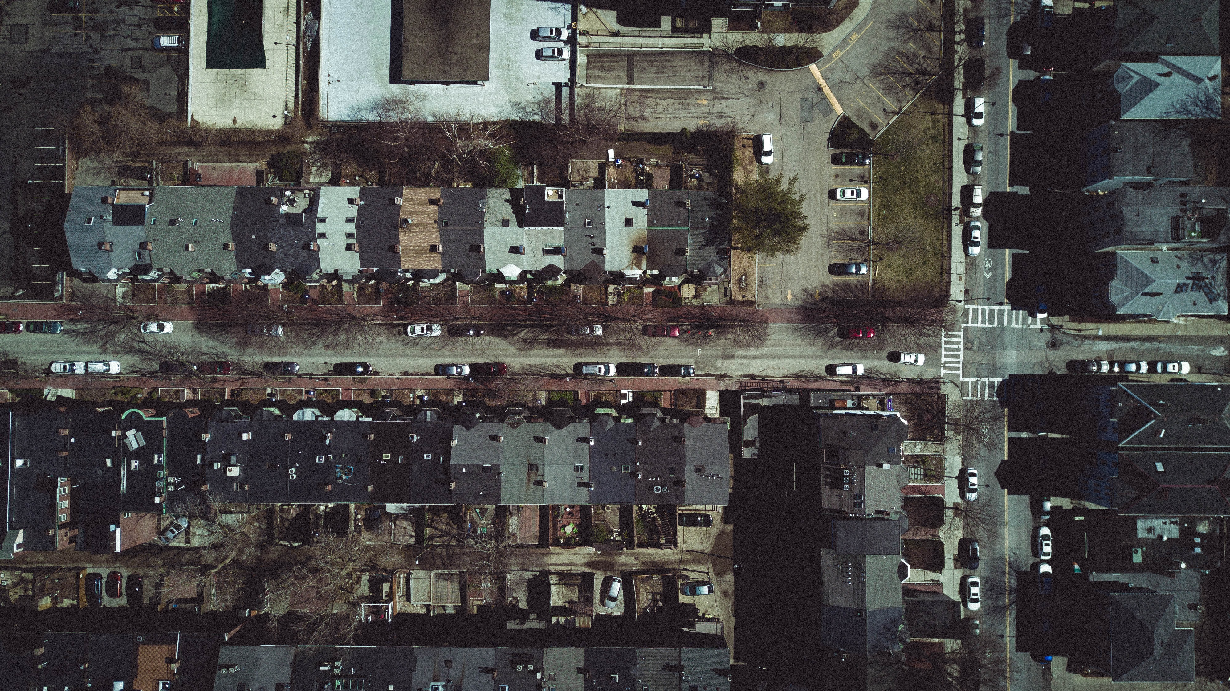 Drone view of suburbs, house roofs, and cars on streets
