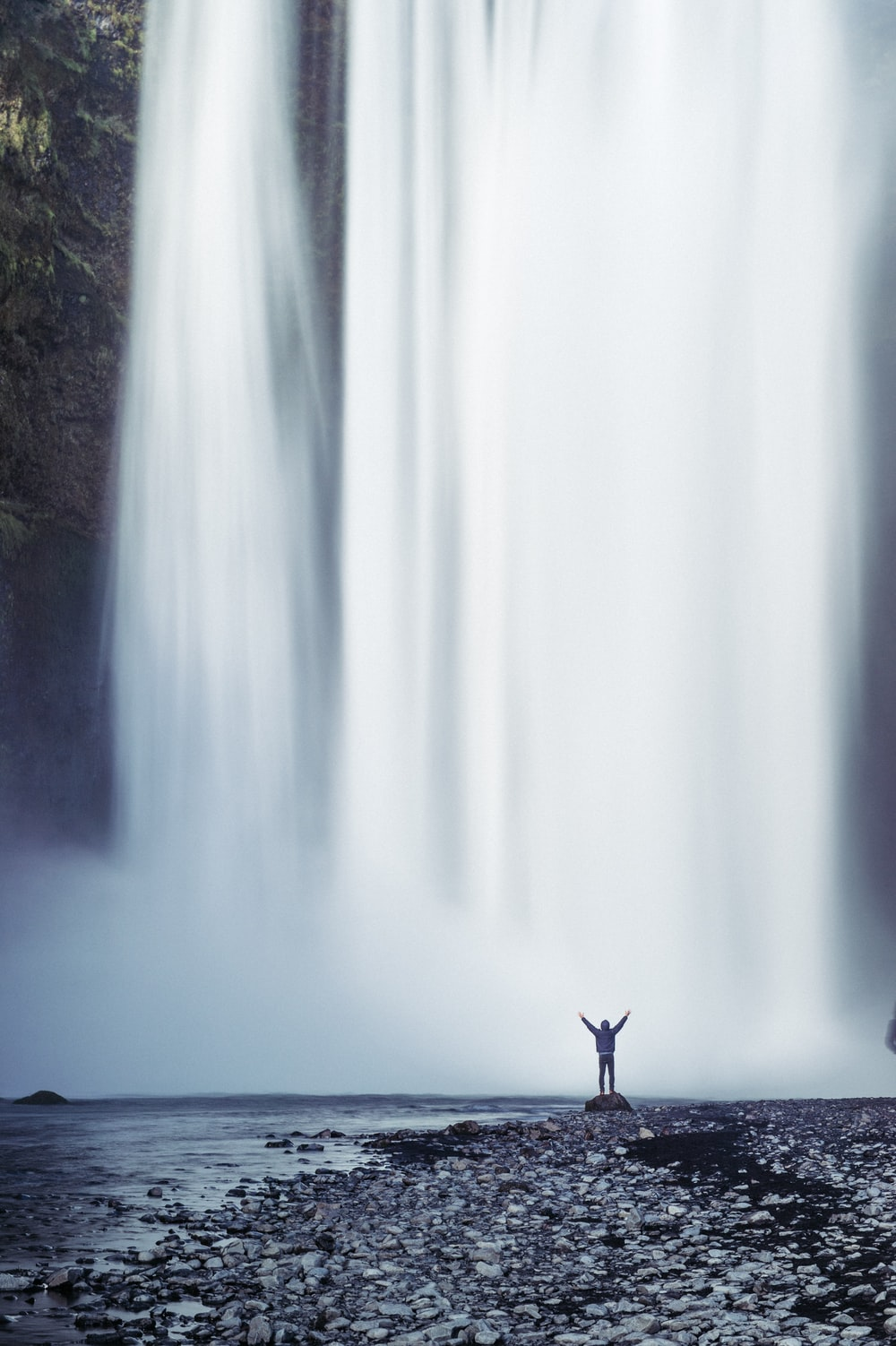 person standing beside waterfall